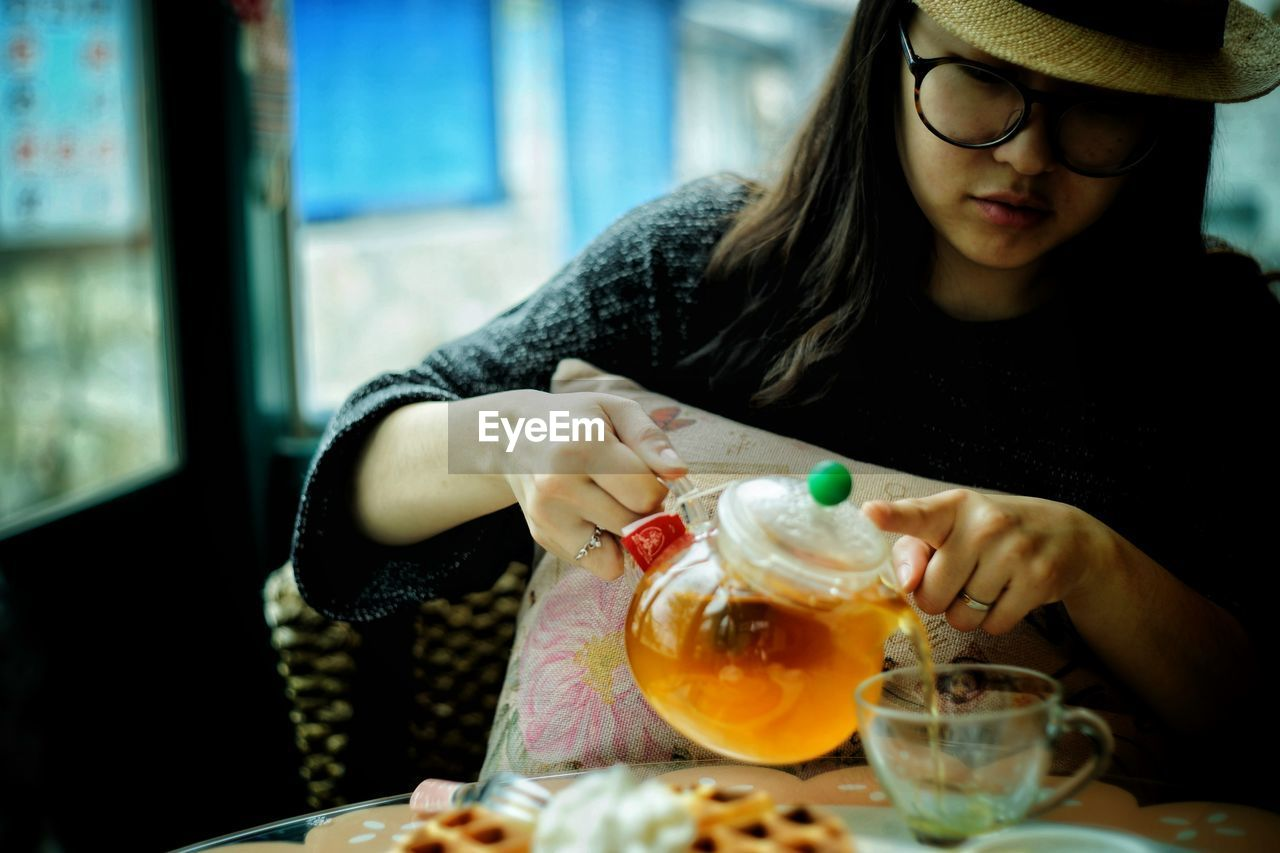 Young Woman Pouring Tea From Pot In Cup