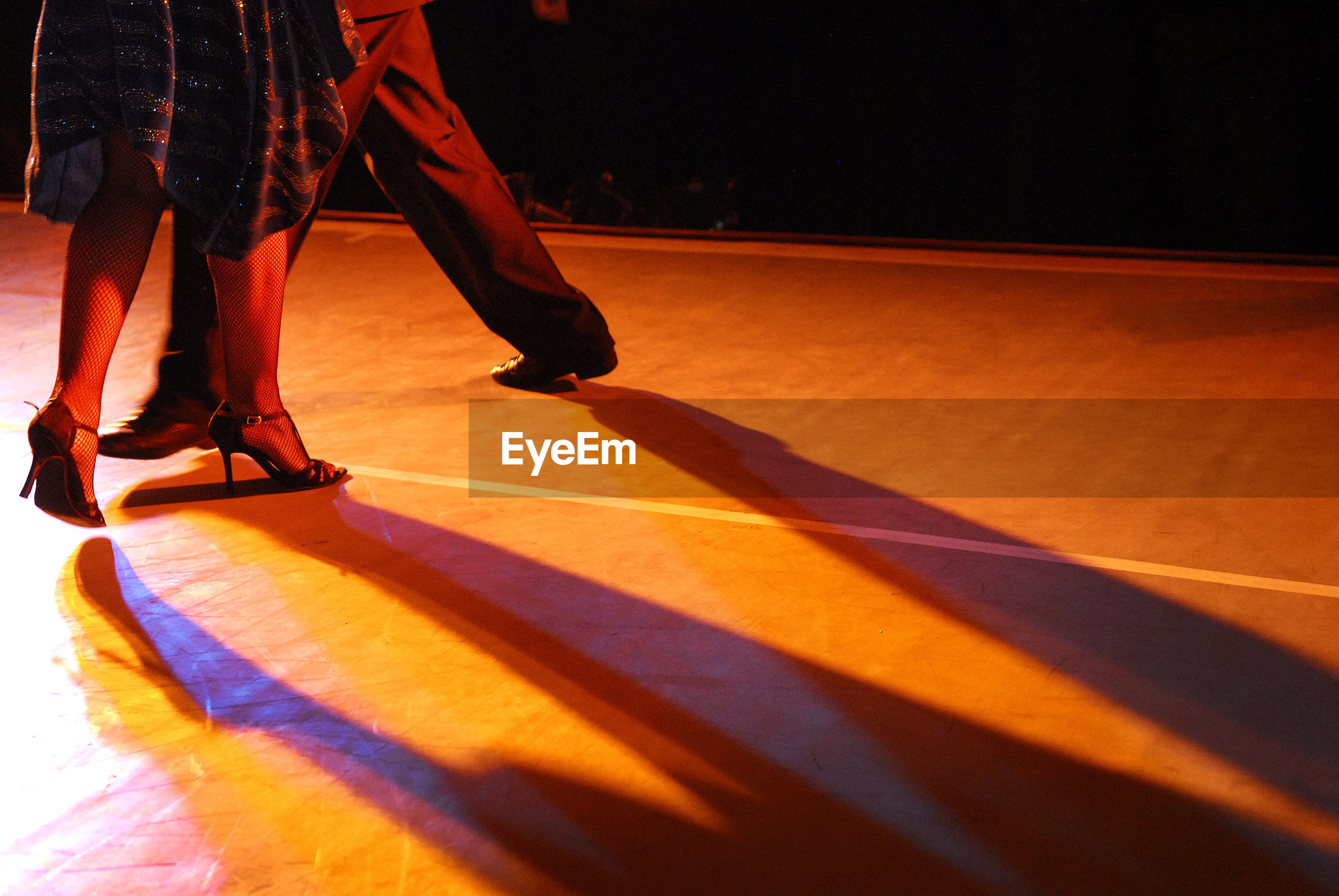Low section of couple dancing on floor