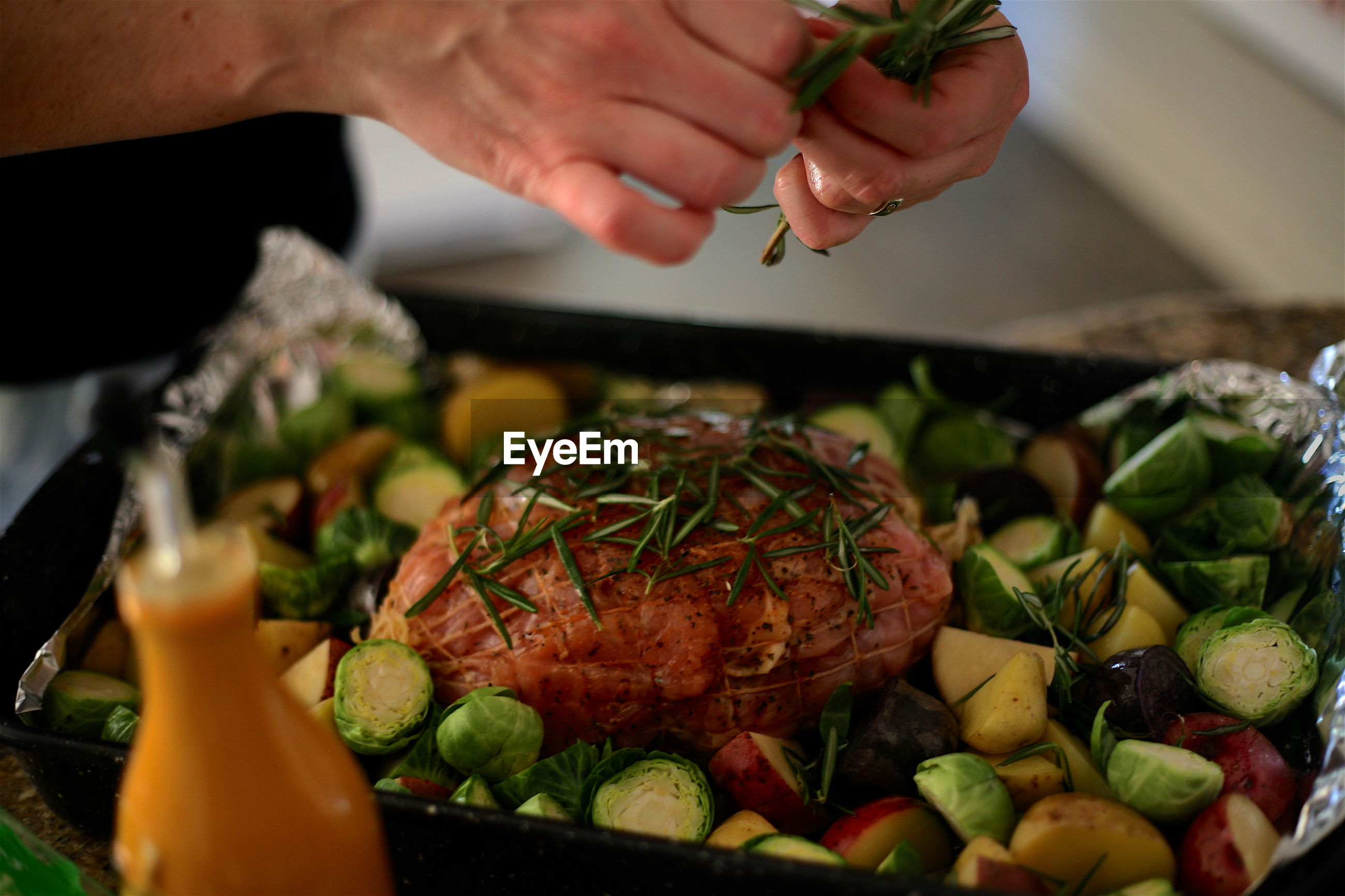 Cropped image of hands garnishing meat with rosemary in baking sheet