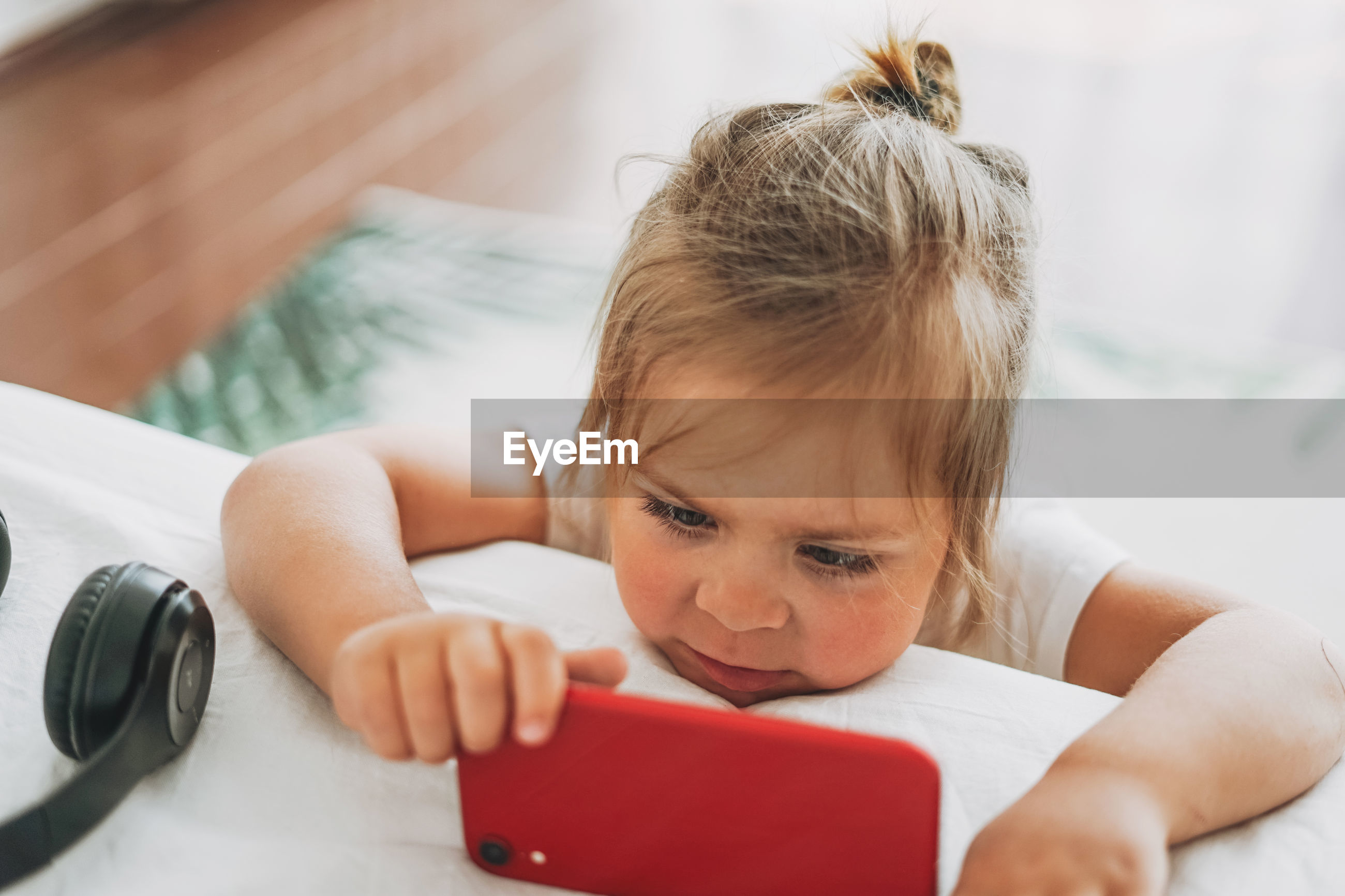Close-up portrait of cute girl using laptop on bed at home