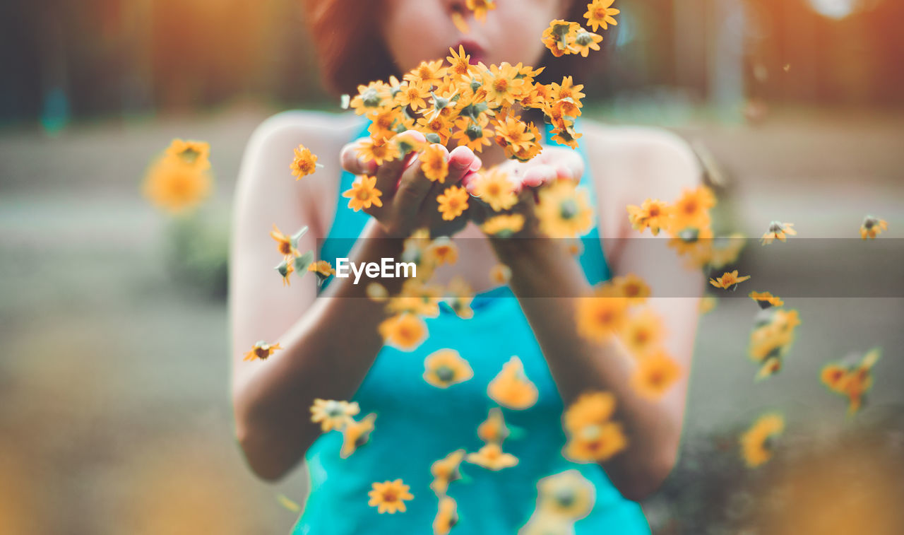 Midsection Of Woman Blowing Flowers