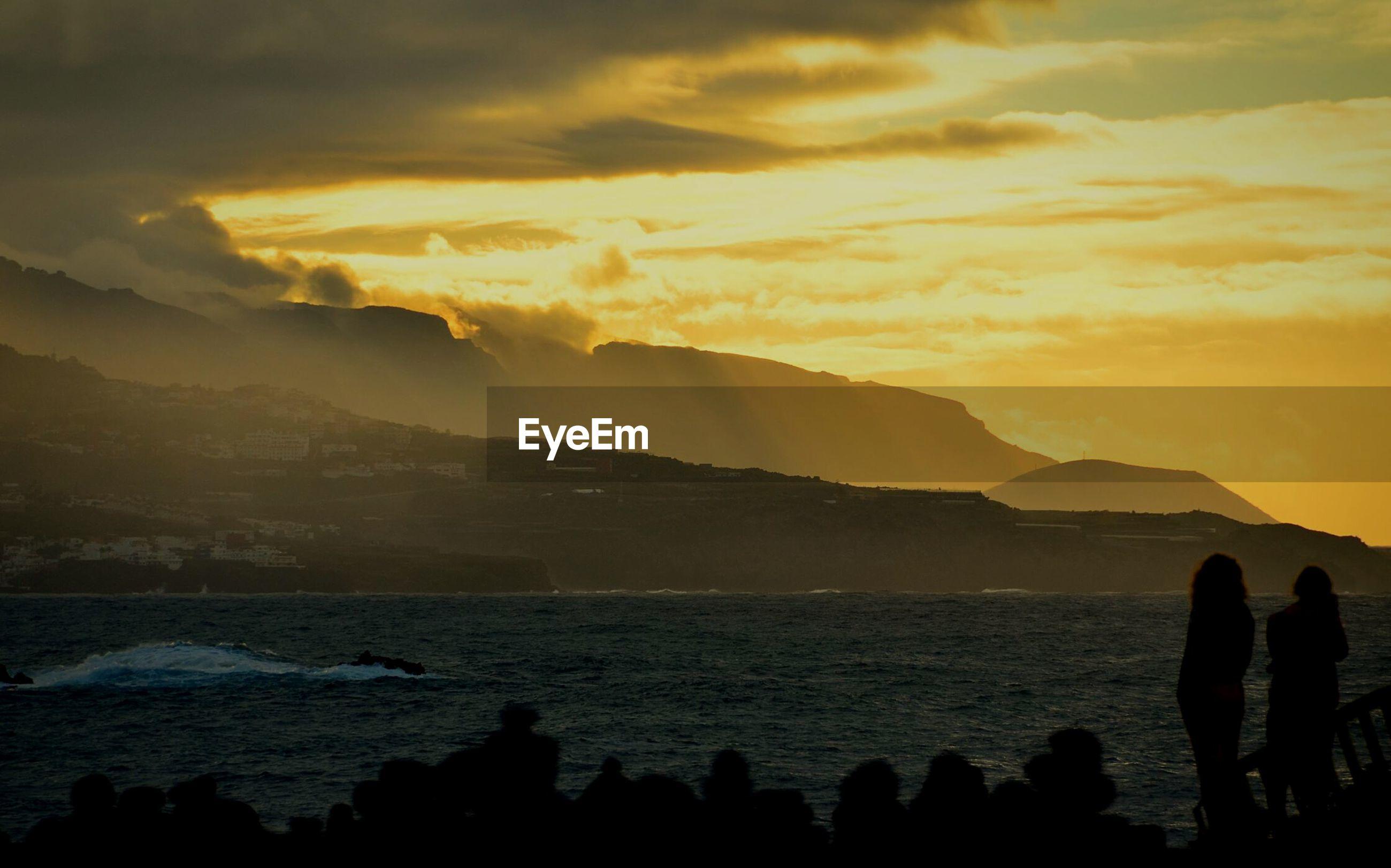 Silhouette of people on coast