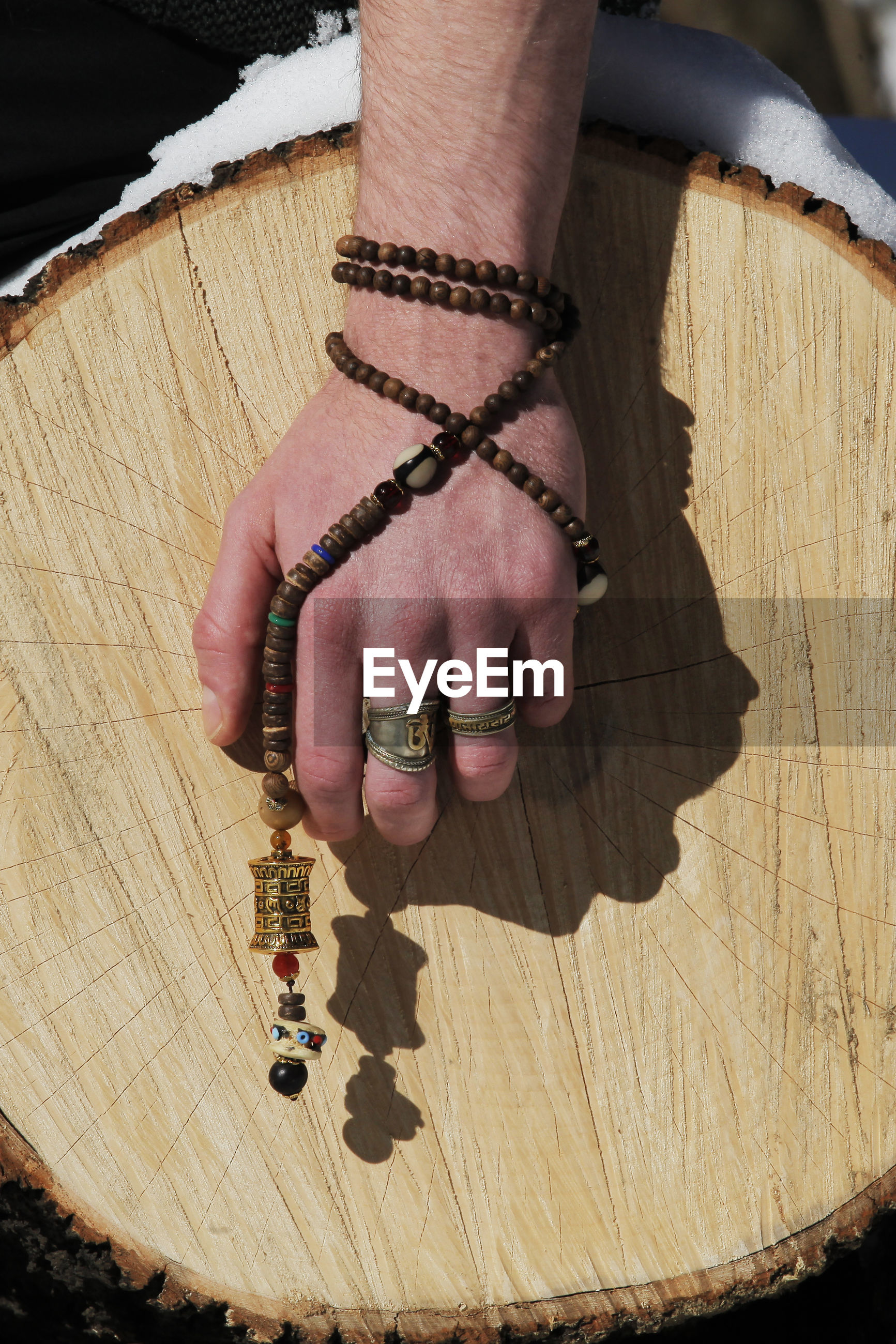 Cropped hand holding bead necklace with pendant against log during winter