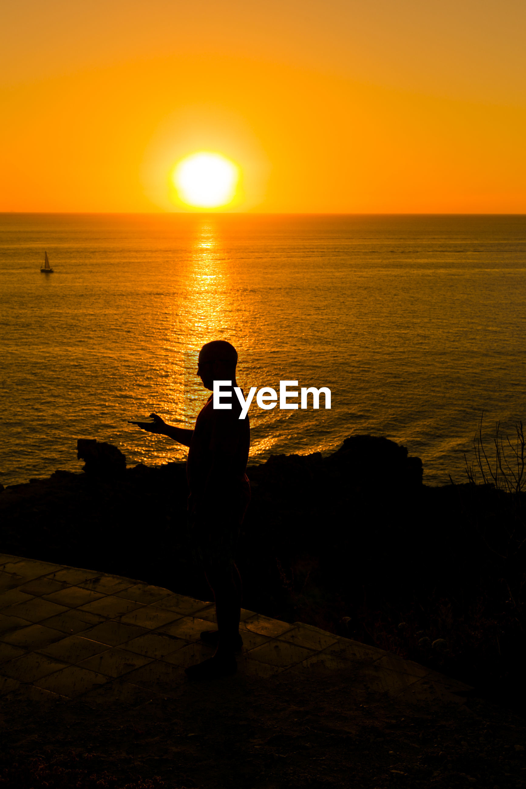Side view of silhouette man standing against sea during sunset