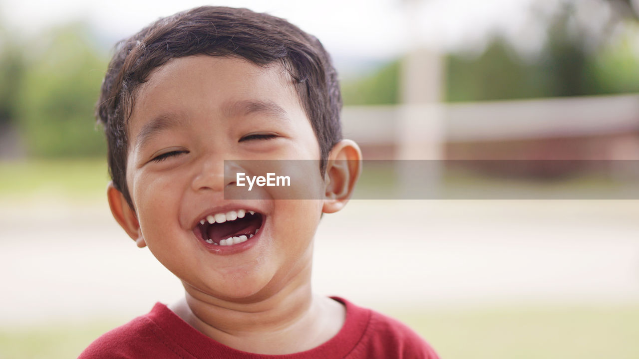 portrait, headshot, childhood, boys, child, men, males, one person, front view, happiness, smiling, focus on foreground, real people, emotion, teeth, close-up, toothy smile, innocence, leisure activity, mouth open, outdoors, gap toothed, human face