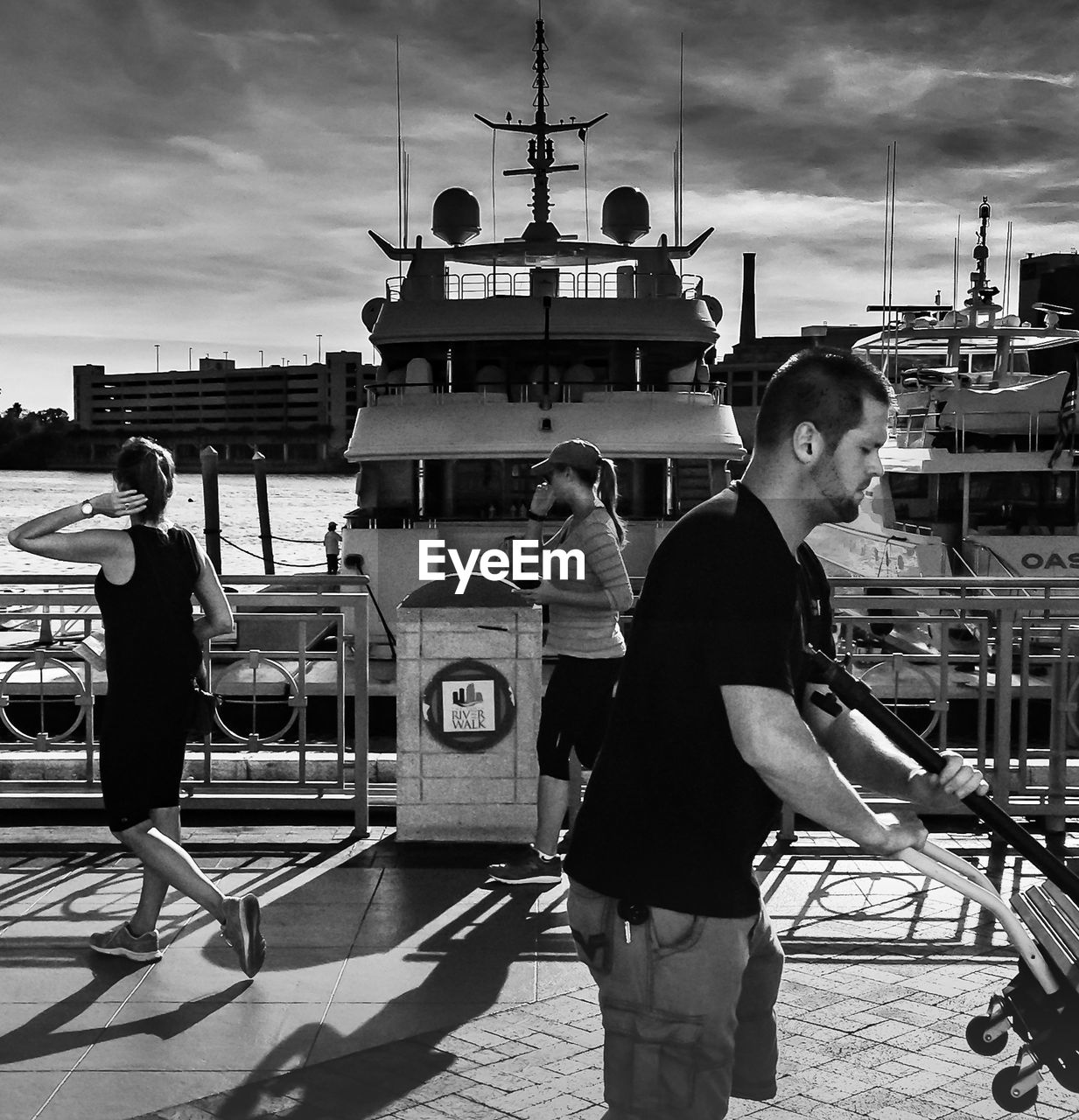 real people, nautical vessel, sky, harbor, transportation, built structure, cloud - sky, mode of transport, outdoors, standing, building exterior, architecture, day, young adult, moored, lifestyles, men, full length, one person, young women, people
