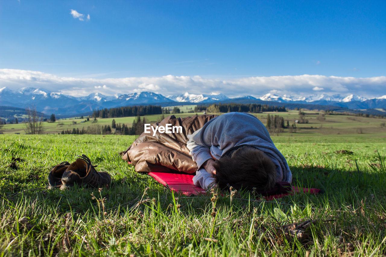 Young Man Sleeping On Green Sunny Field
