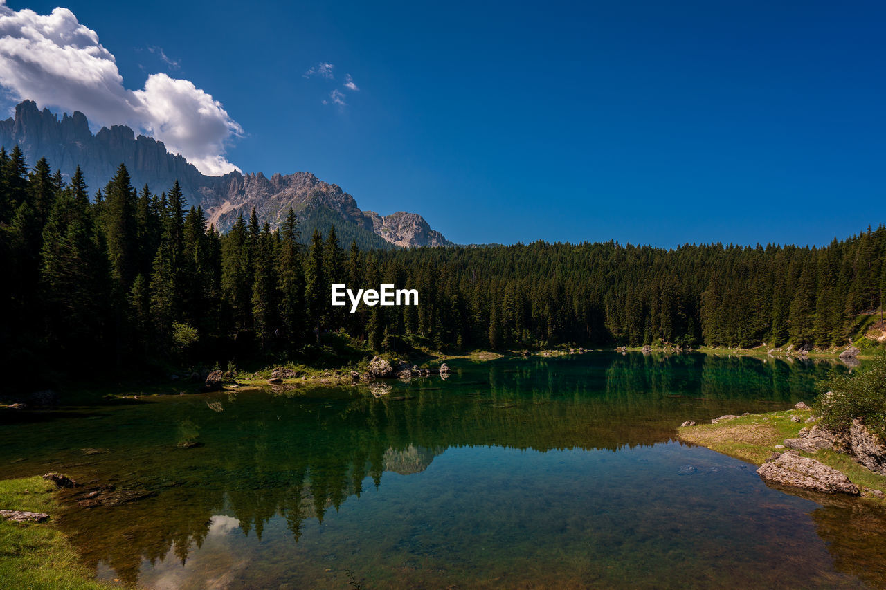 Reflection of trees and mountains in lake against sky