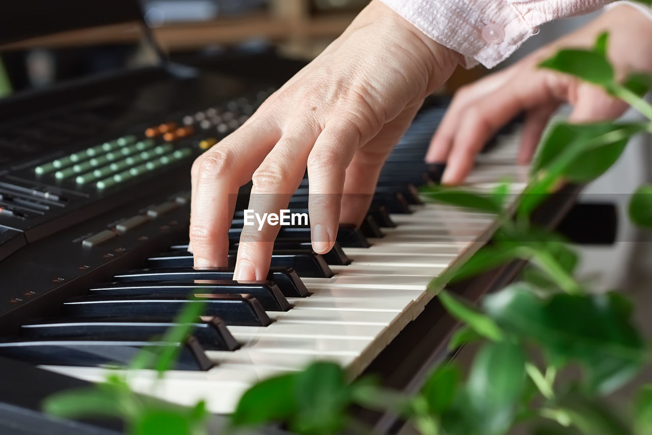 Female musician playing the digital piano or electronic keyboard at home. music education online