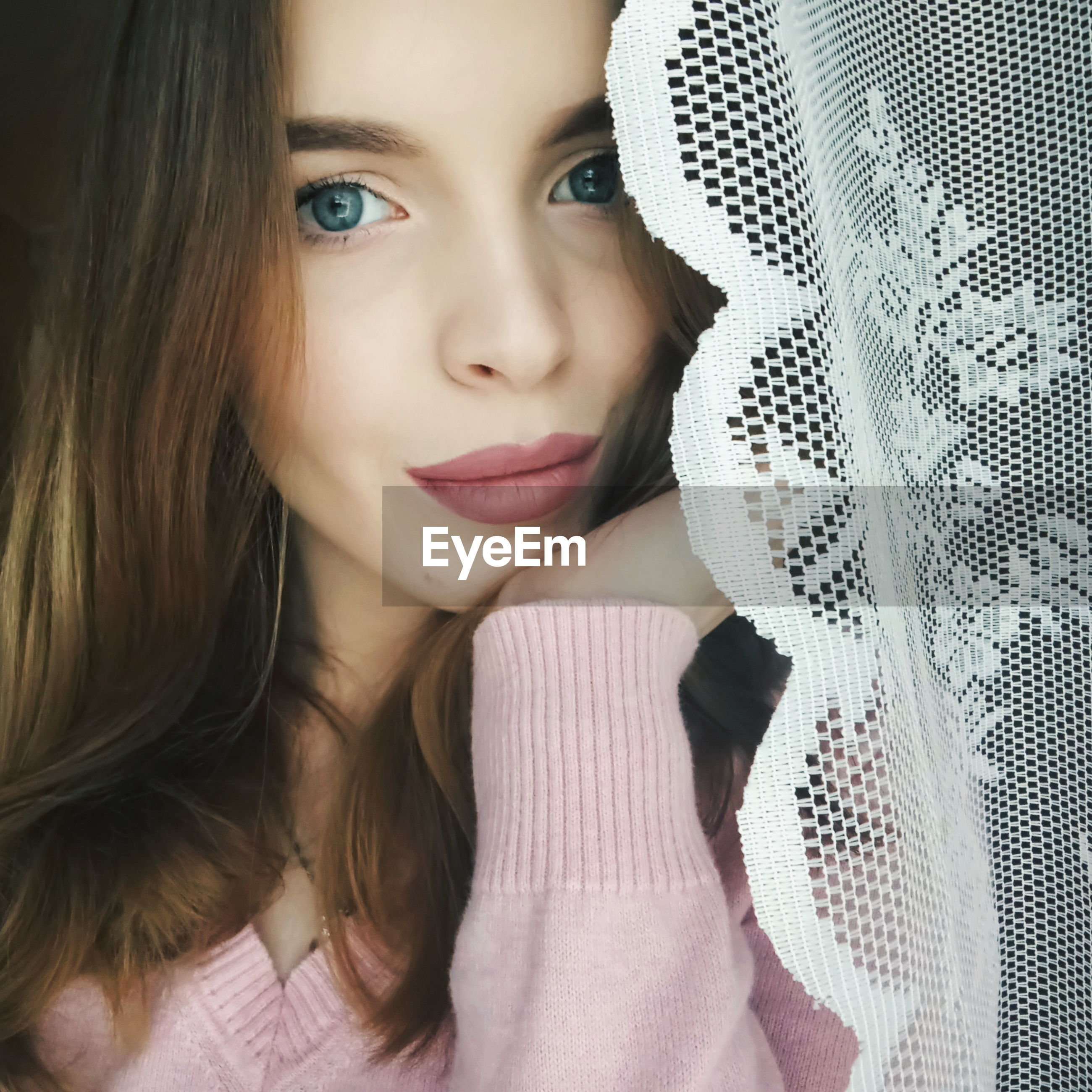 Close-up portrait of beautiful woman by curtain