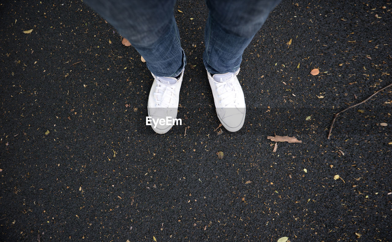 low section, shoe, human leg, standing, body part, one person, high angle view, human body part, real people, day, casual clothing, lifestyles, men, jeans, leisure activity, outdoors, unrecognizable person, human foot, nature, human limb, leather, leaves