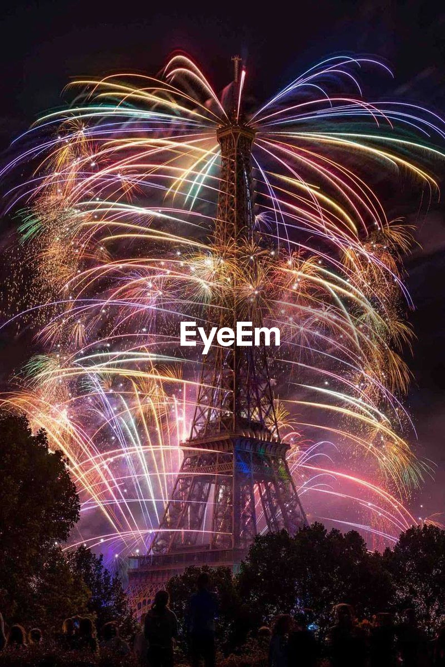 illuminated, night, long exposure, motion, arts culture and entertainment, celebration, firework display, multi colored, low angle view, blurred motion, firework - man made object, sky, glowing, exploding, light trail, built structure, tree, ferris wheel, architecture, event