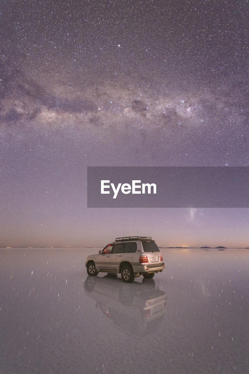CAR ON STREET AGAINST SKY AT NIGHT