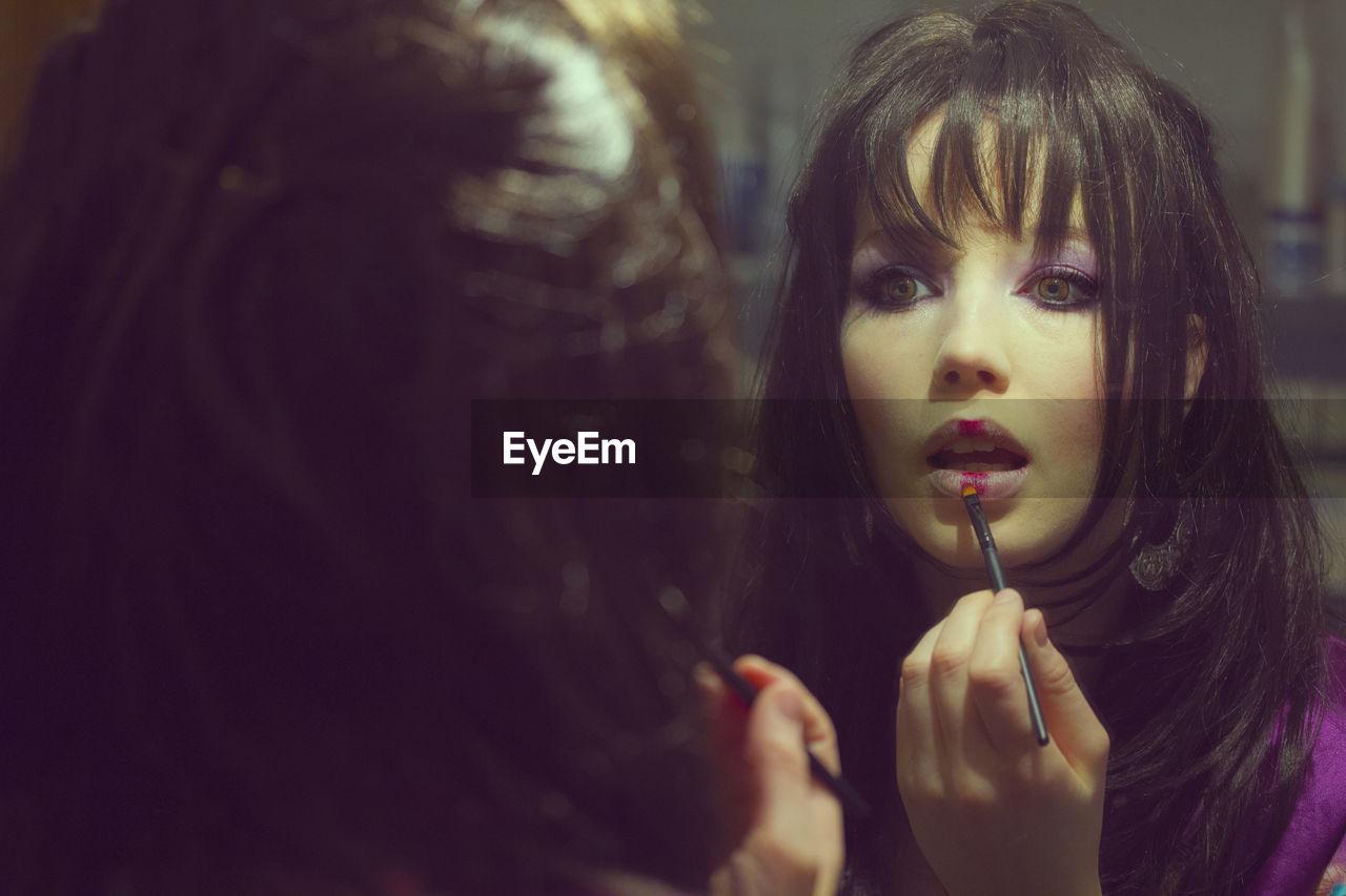 Woman Applying Lip Gloss Reflecting On Mirror