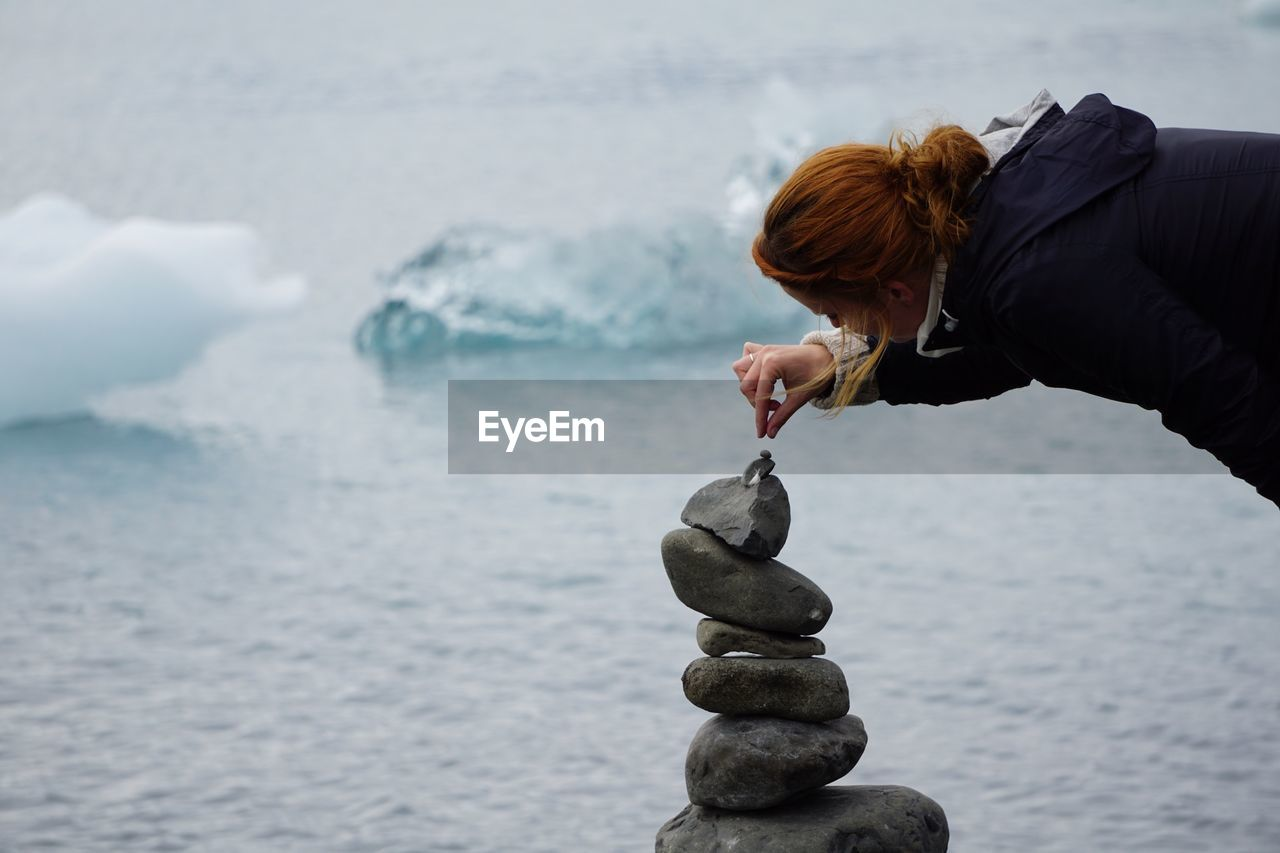 Woman Making Stack Of Stones Against Sea