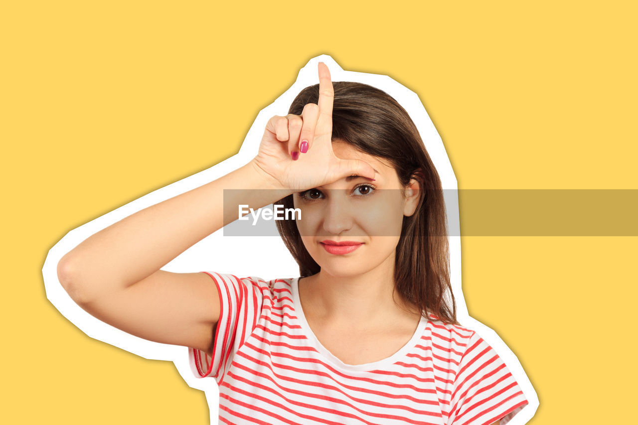 Portrait of smiling young woman gesturing against yellow background