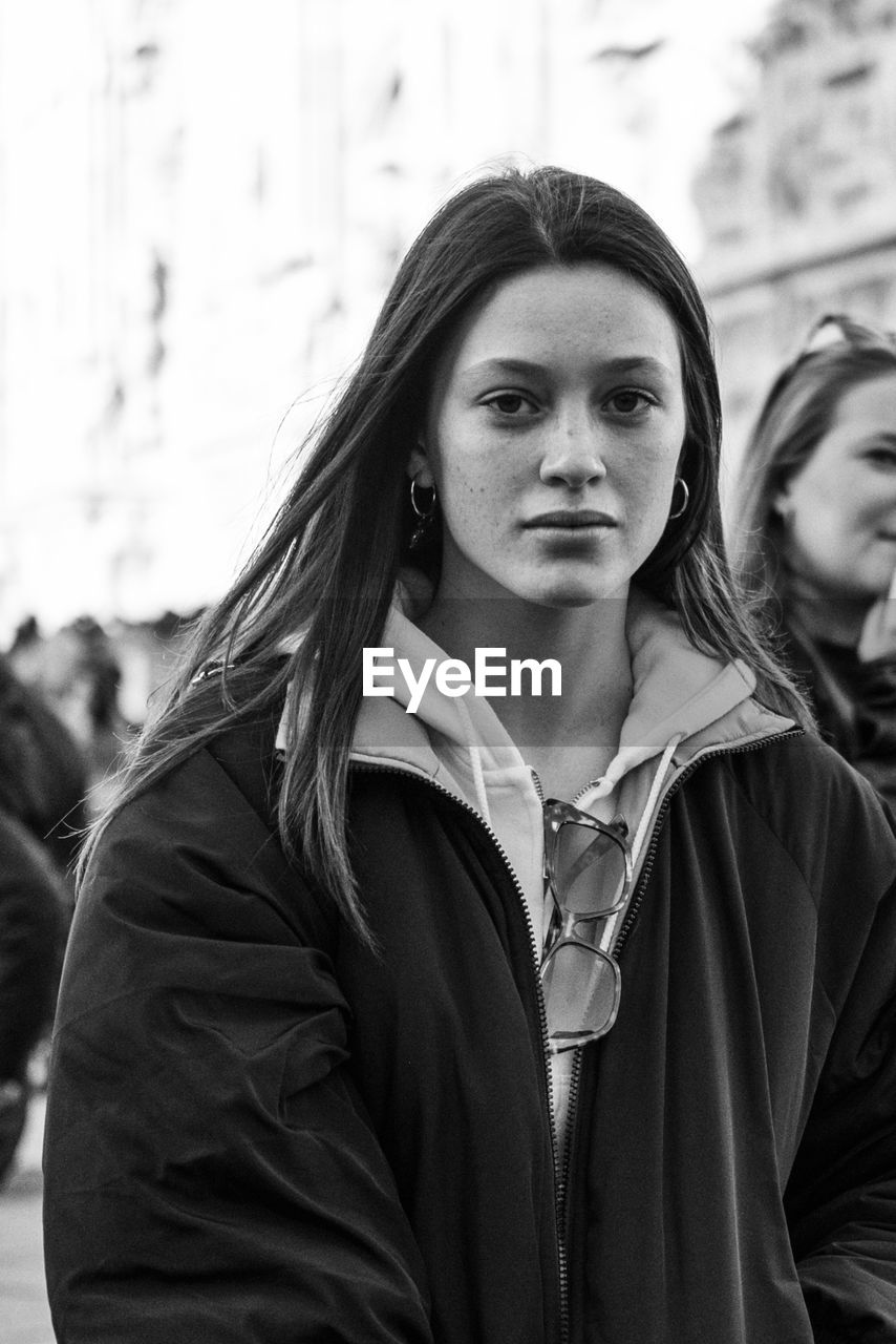 real people, lifestyles, focus on foreground, portrait, front view, young adult, leisure activity, young women, people, waist up, women, clothing, standing, adult, headshot, looking at camera, casual clothing, day, contemplation, beautiful woman, hood - clothing, teenager, hairstyle, warm clothing