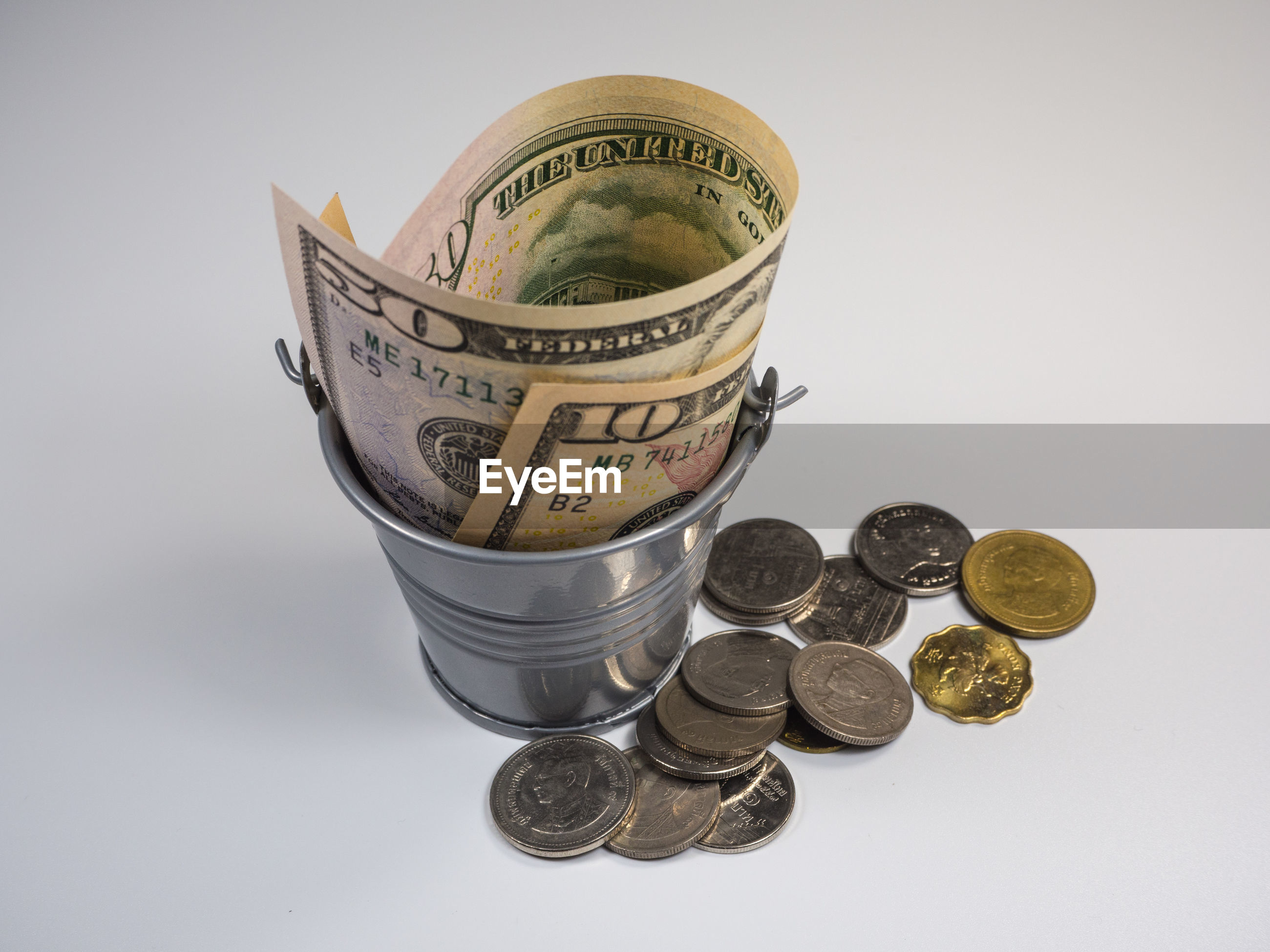 High angle view of paper currency in bucket by coins against gray background