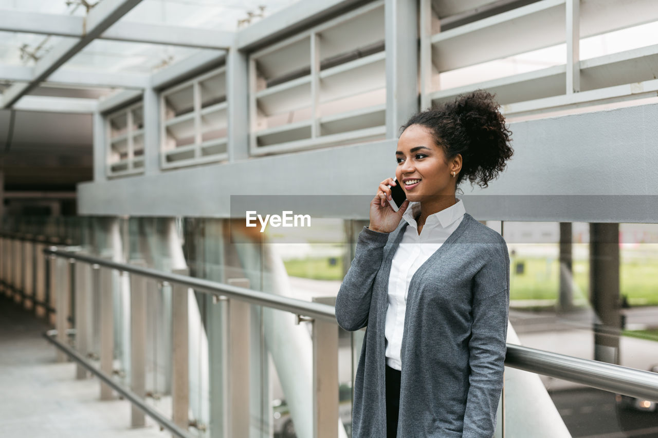 Businesswoman Using Phone While Standing By Railing