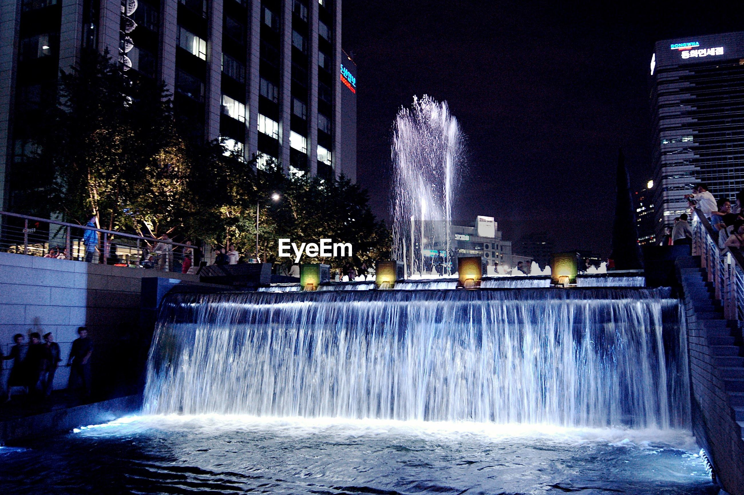 water, night, building exterior, long exposure, motion, architecture, built structure, illuminated, fountain, splashing, waterfront, spraying, city, flowing water, blurred motion, reflection, waterfall, building, outdoors, river
