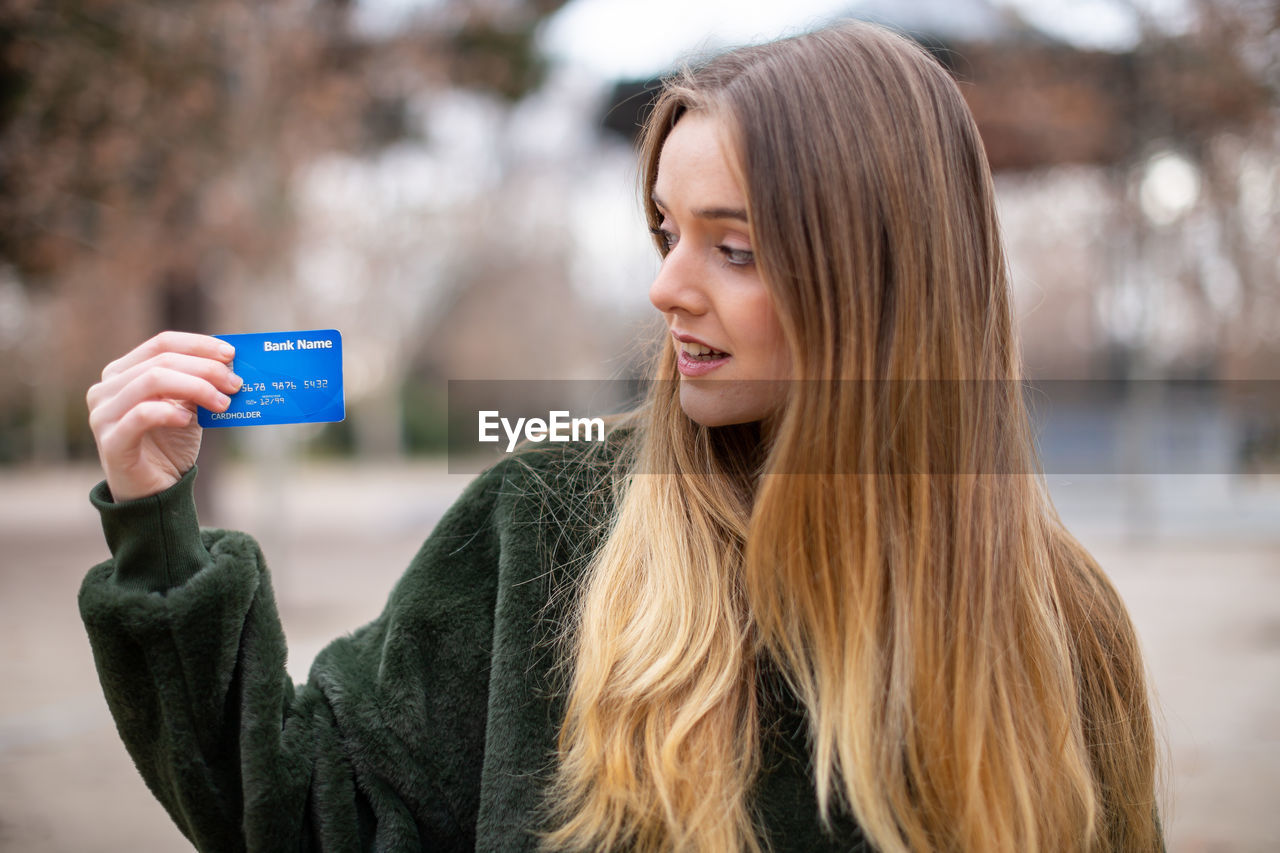 Woman holding credit card while standing in park