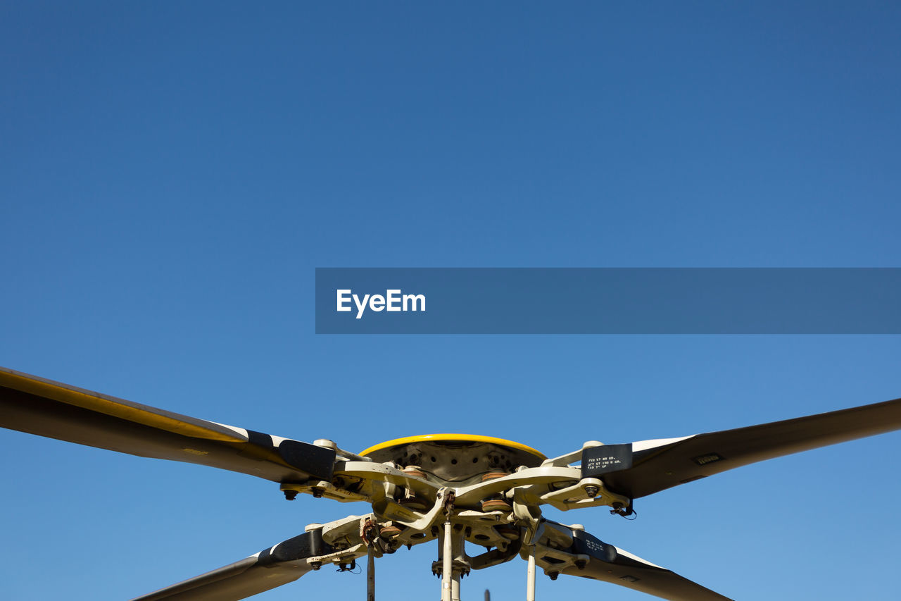 Close-Up Of Helicopter Propeller Against Blue Sky