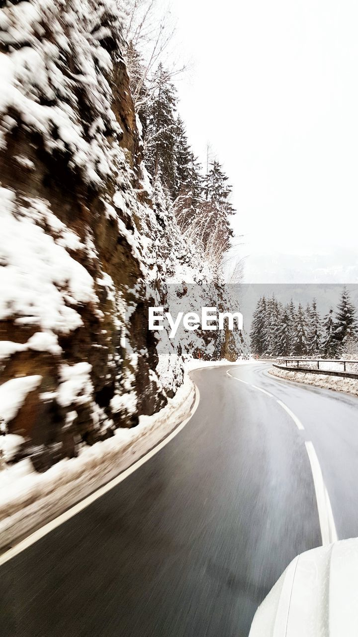 Car on street during snowfall by rock formation