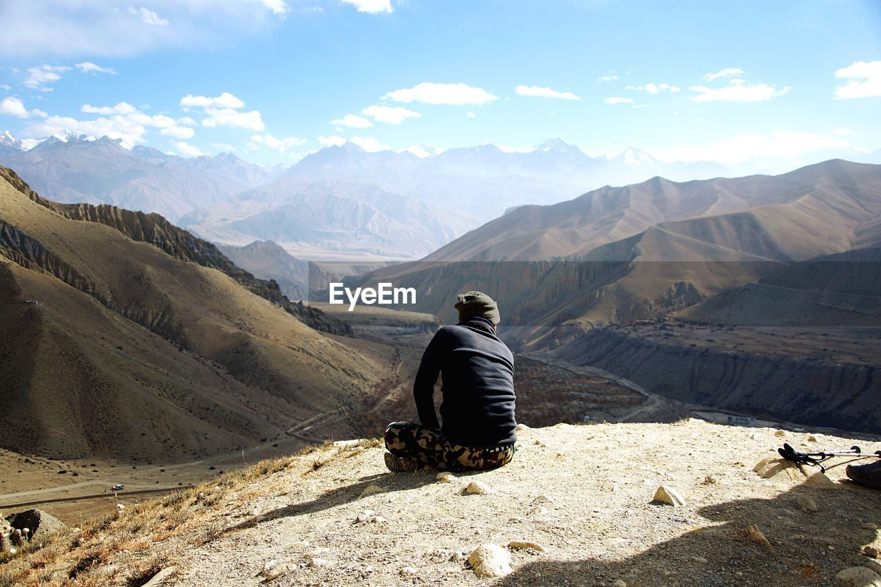 REAR VIEW OF MAN ON MOUNTAIN AGAINST SKY