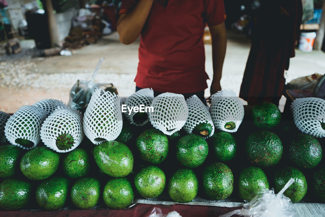 Midsection Of Vendor Selling Fruits At Market