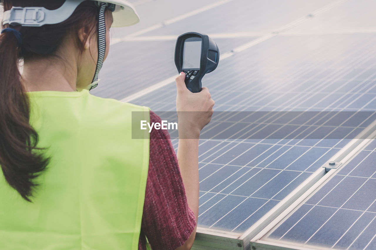 technology, one person, real people, lifestyles, environmental conservation, rear view, holding, nature, clothing, environment, adult, leisure activity, day, women, renewable energy, alternative energy, solar energy, fuel and power generation, solar panel, outdoors