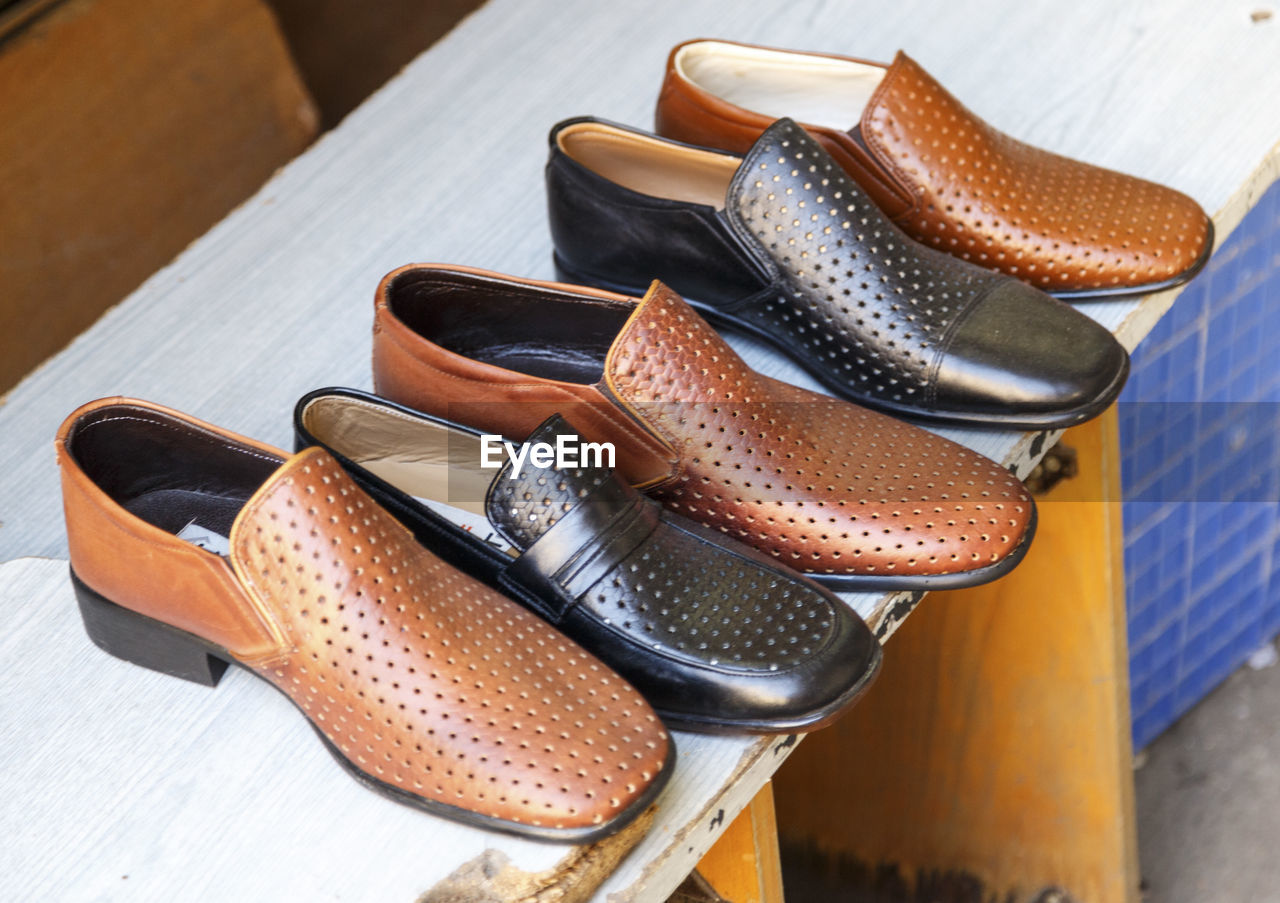 High angle view of leather shoes on table for sale in market
