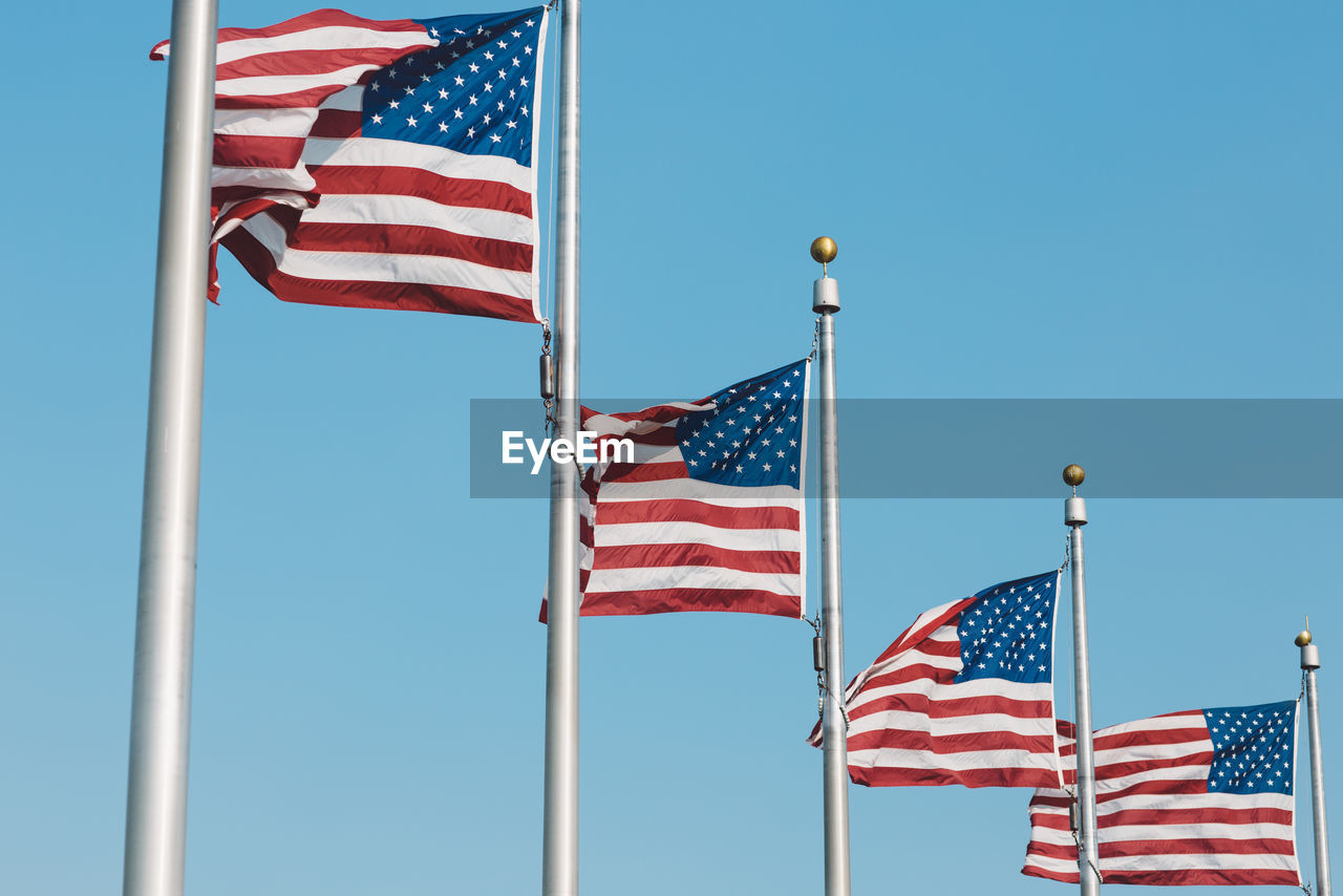 Low Angle View Of American Flags Fluttering Against Clear Blue Sky