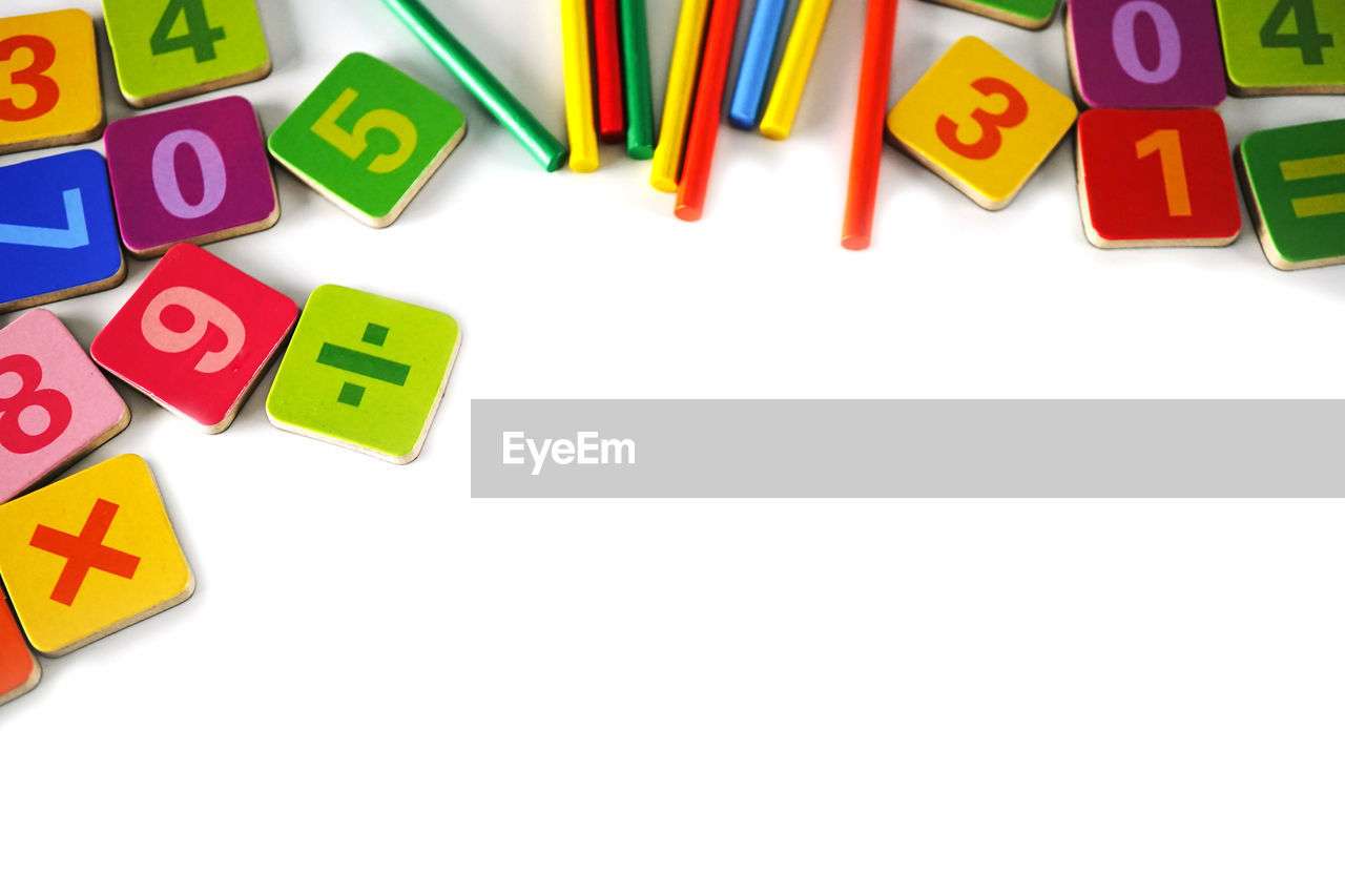Close-Up Of Colorful Pencils And Toy Blocks On White Background