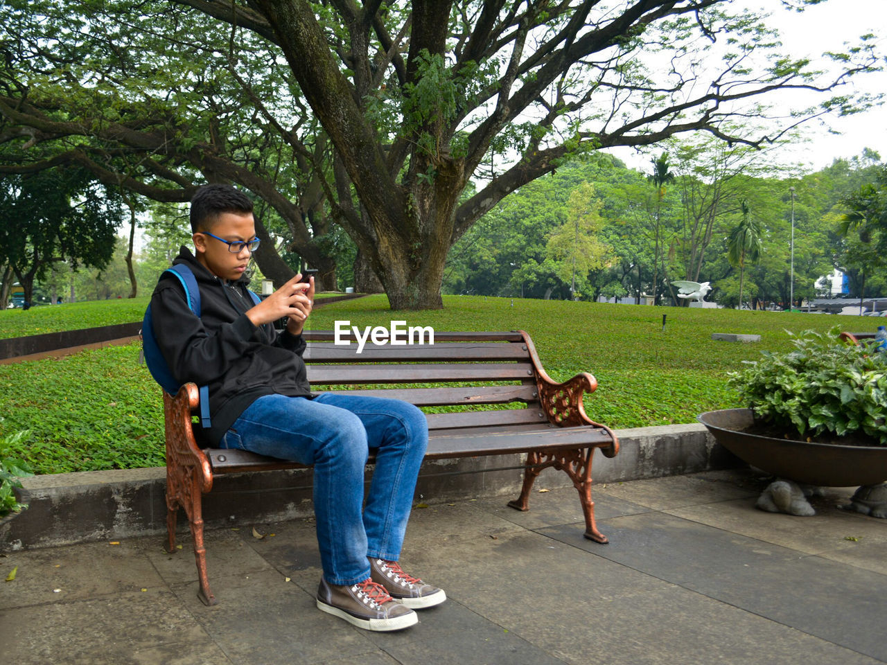 Boy using mobile phone while sitting on bench at park