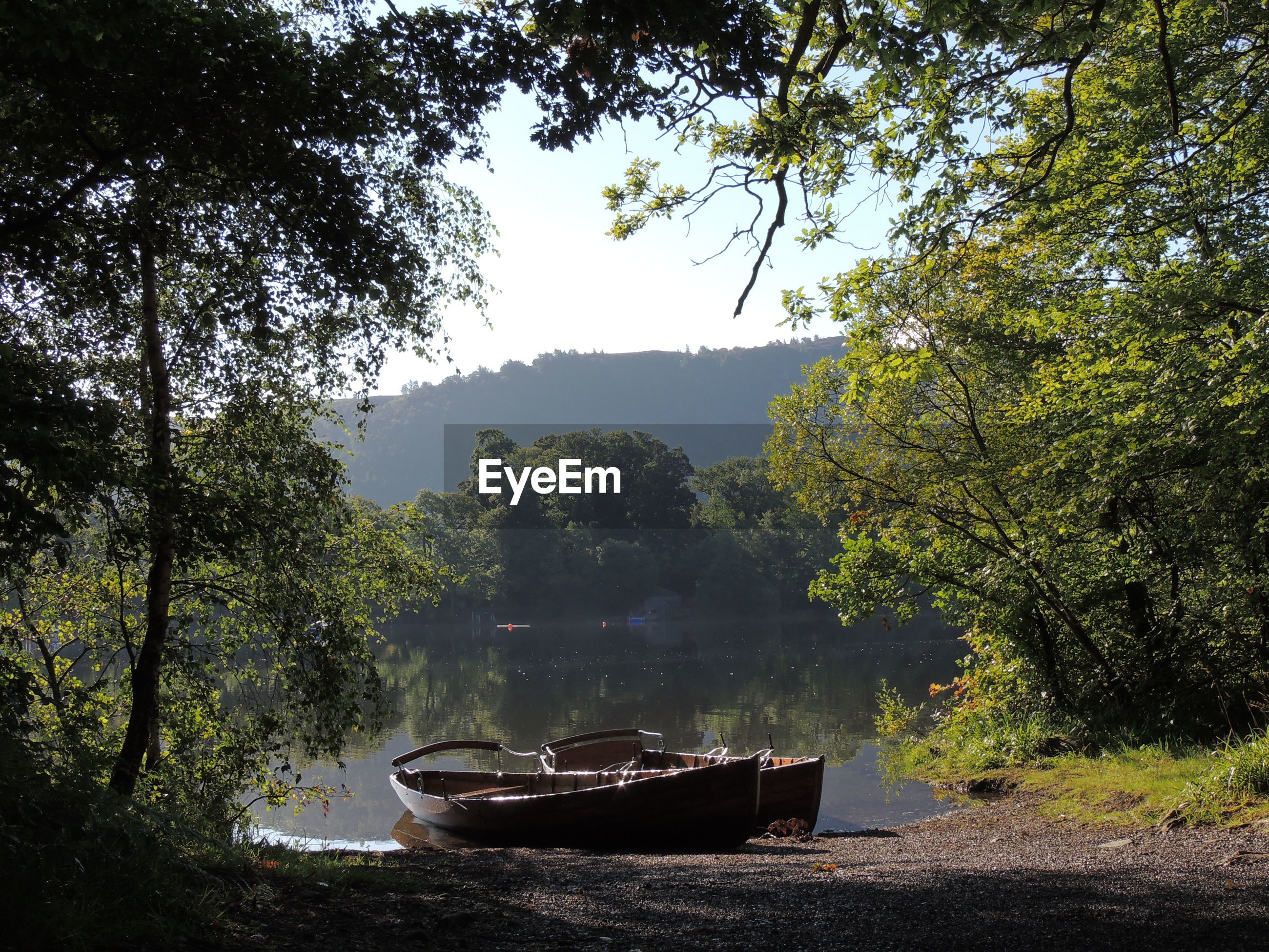 BOAT MOORED IN RIVER AGAINST TREES