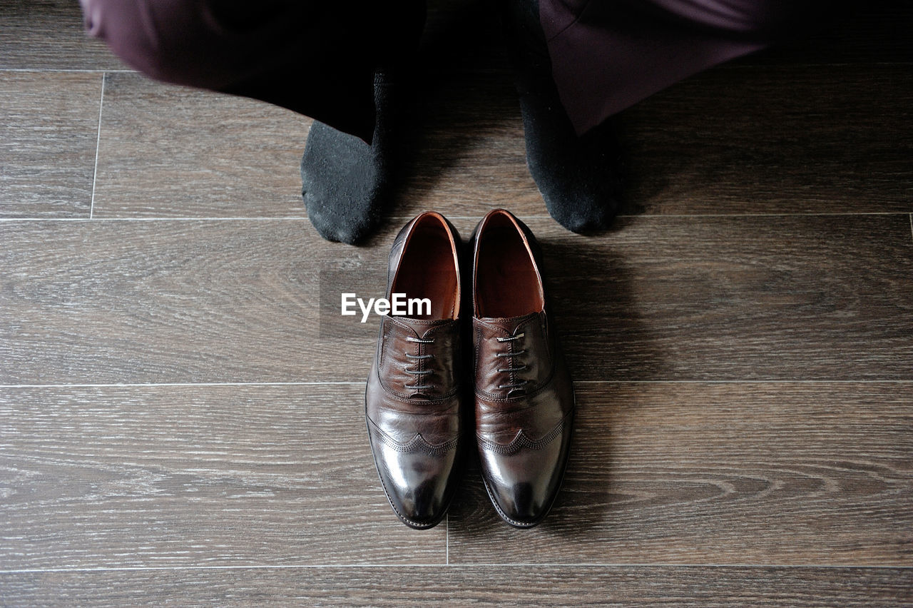 Low section of man wearing shoes on floor