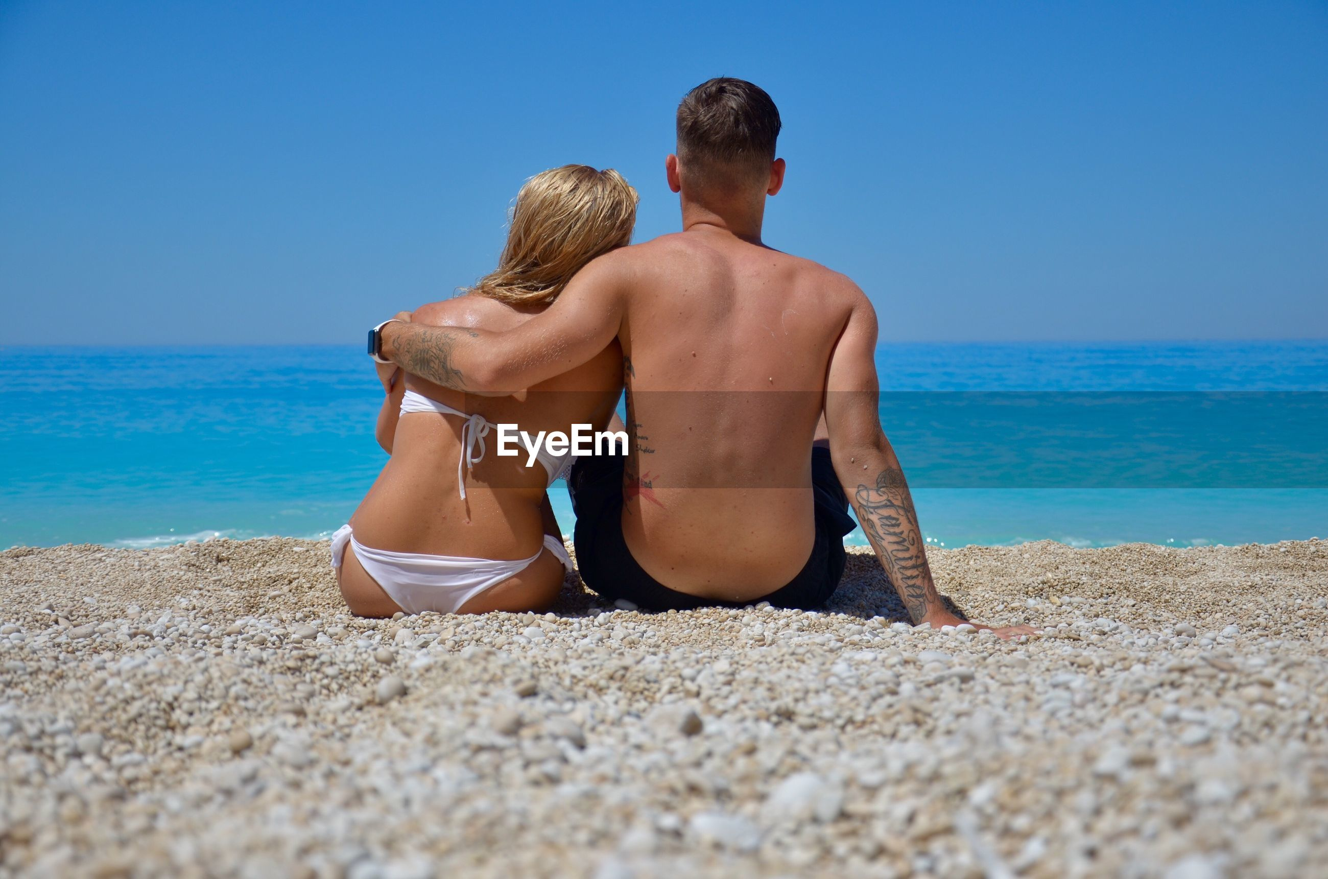 Rear view of man and woman sitting at beach against sky