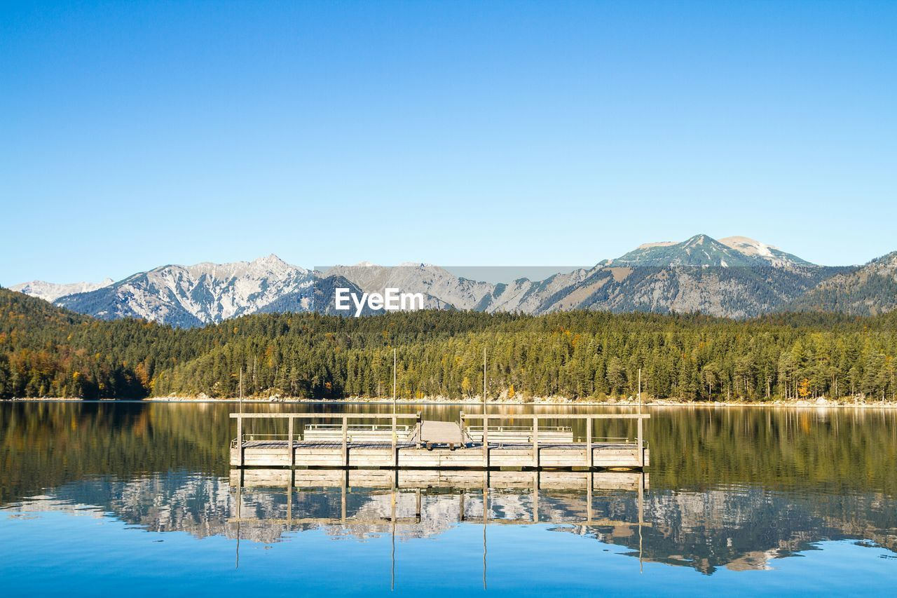 mountain, reflection, water, tranquil scene, tranquility, clear sky, scenics, lake, beauty in nature, nature, copy space, mountain range, blue, waterfront, no people, idyllic, non-urban scene, day, standing water, outdoors, tree, sunlight, sky, landscape
