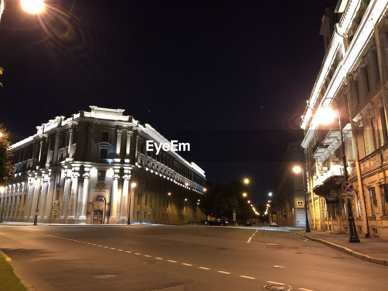 Illuminated buildings at street in city against clear sky