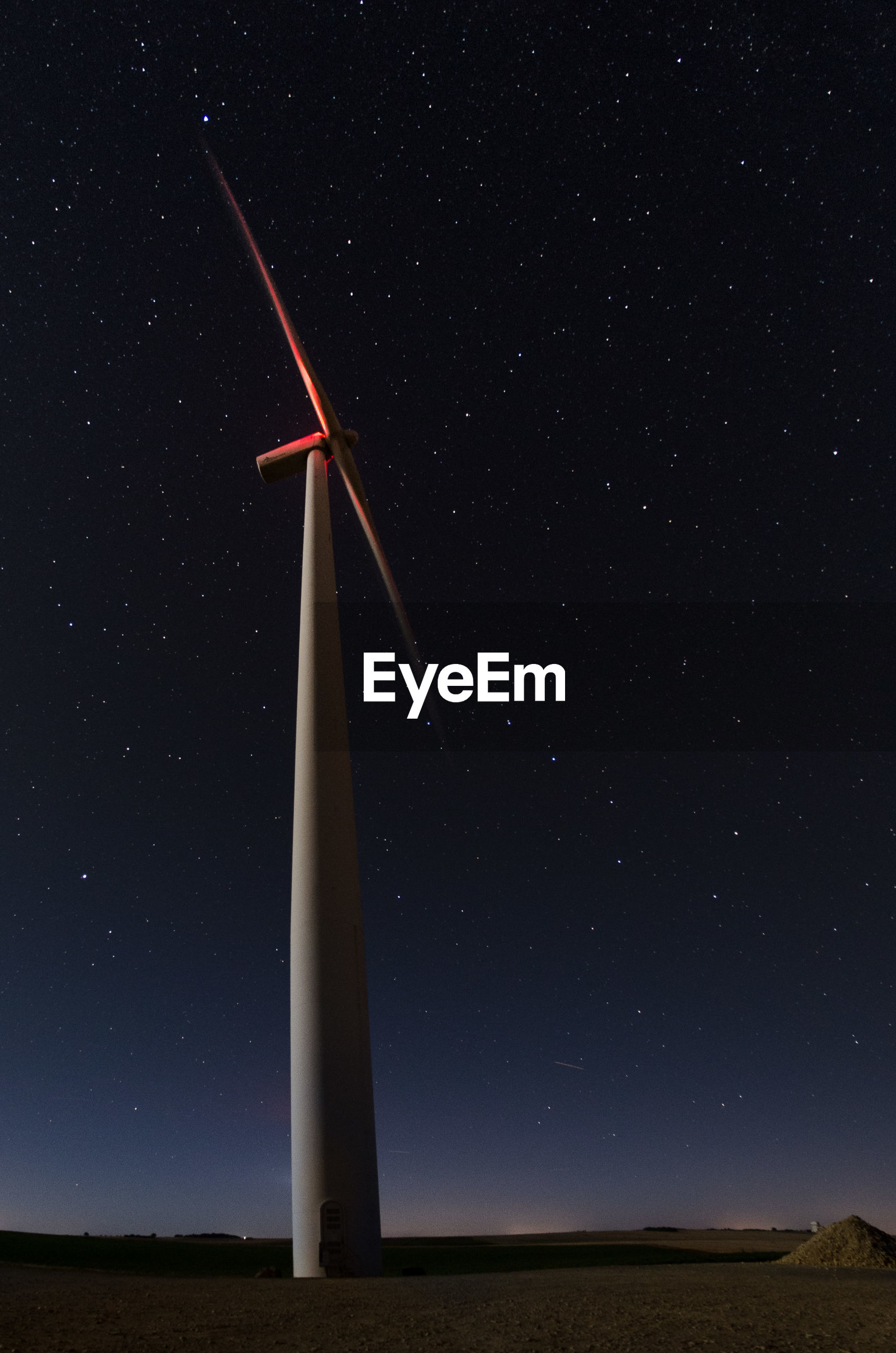 LOW ANGLE VIEW OF WIND TURBINES ON FIELD AGAINST SKY