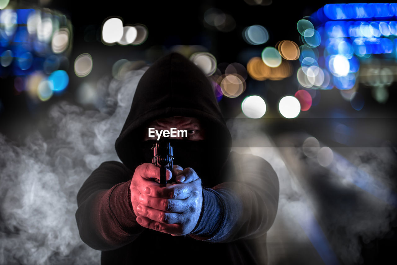 Portrait of criminal wearing mask while aiming gun