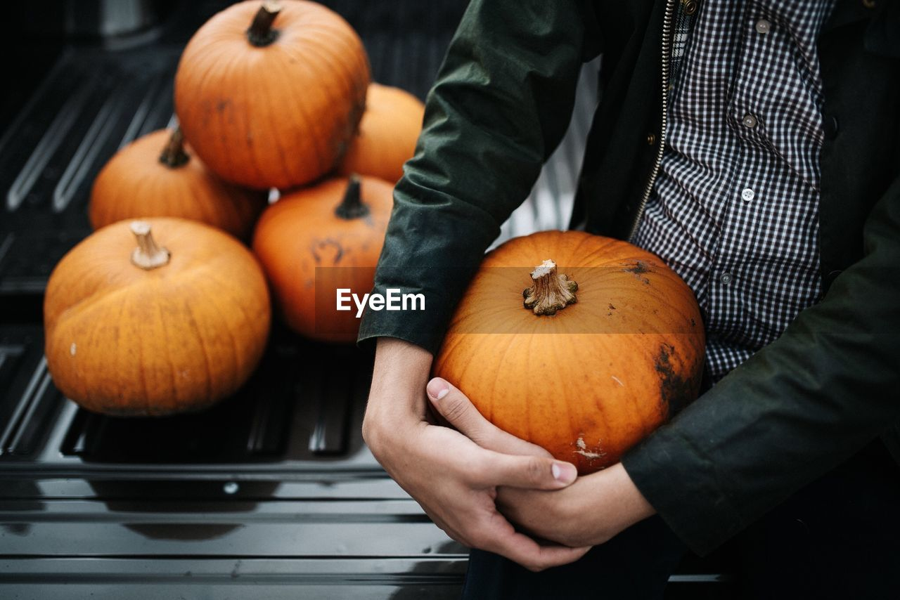 Midsection of man holding pumpkin while sitting outdoors