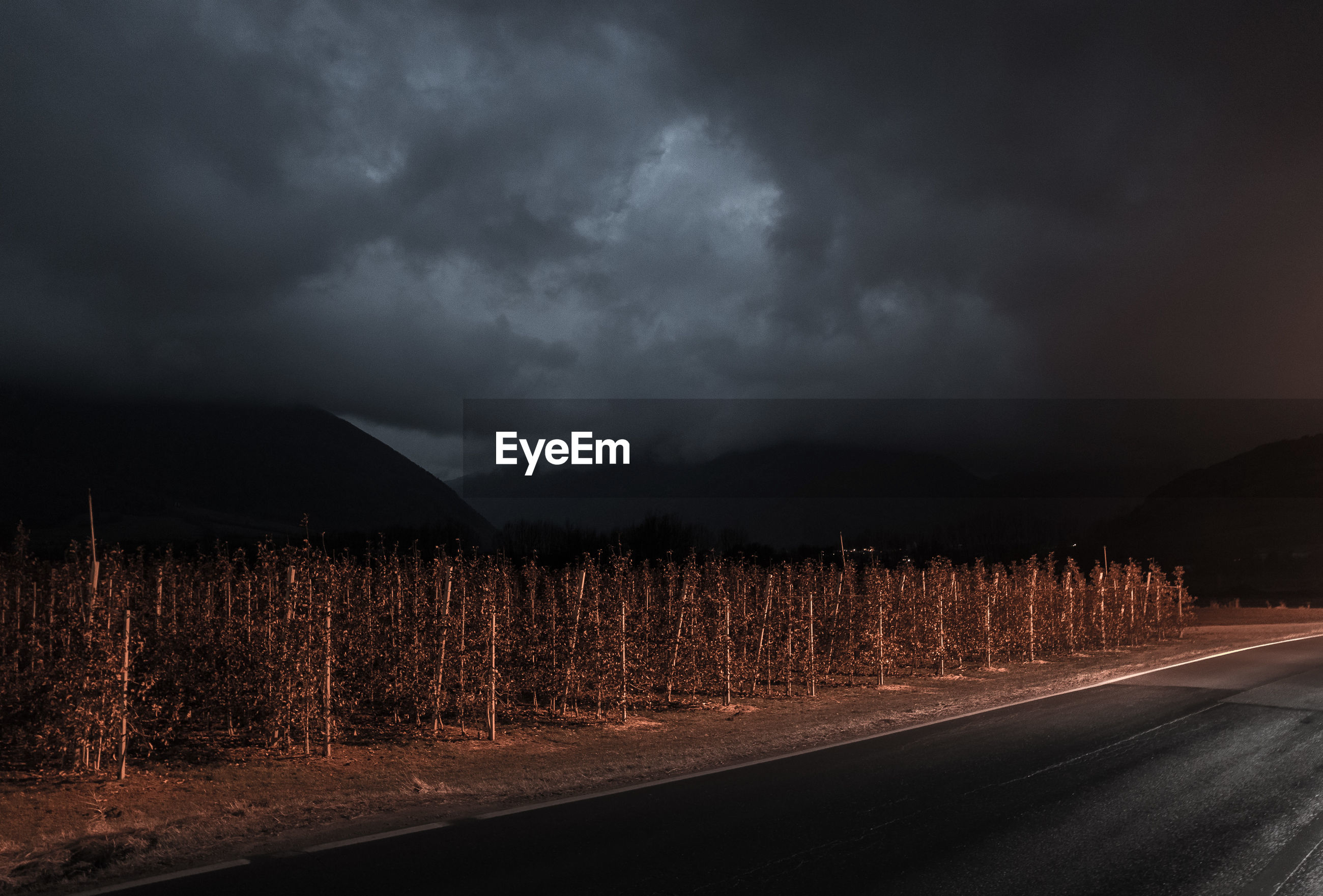 SCENIC VIEW OF ROAD AGAINST STORM CLOUDS