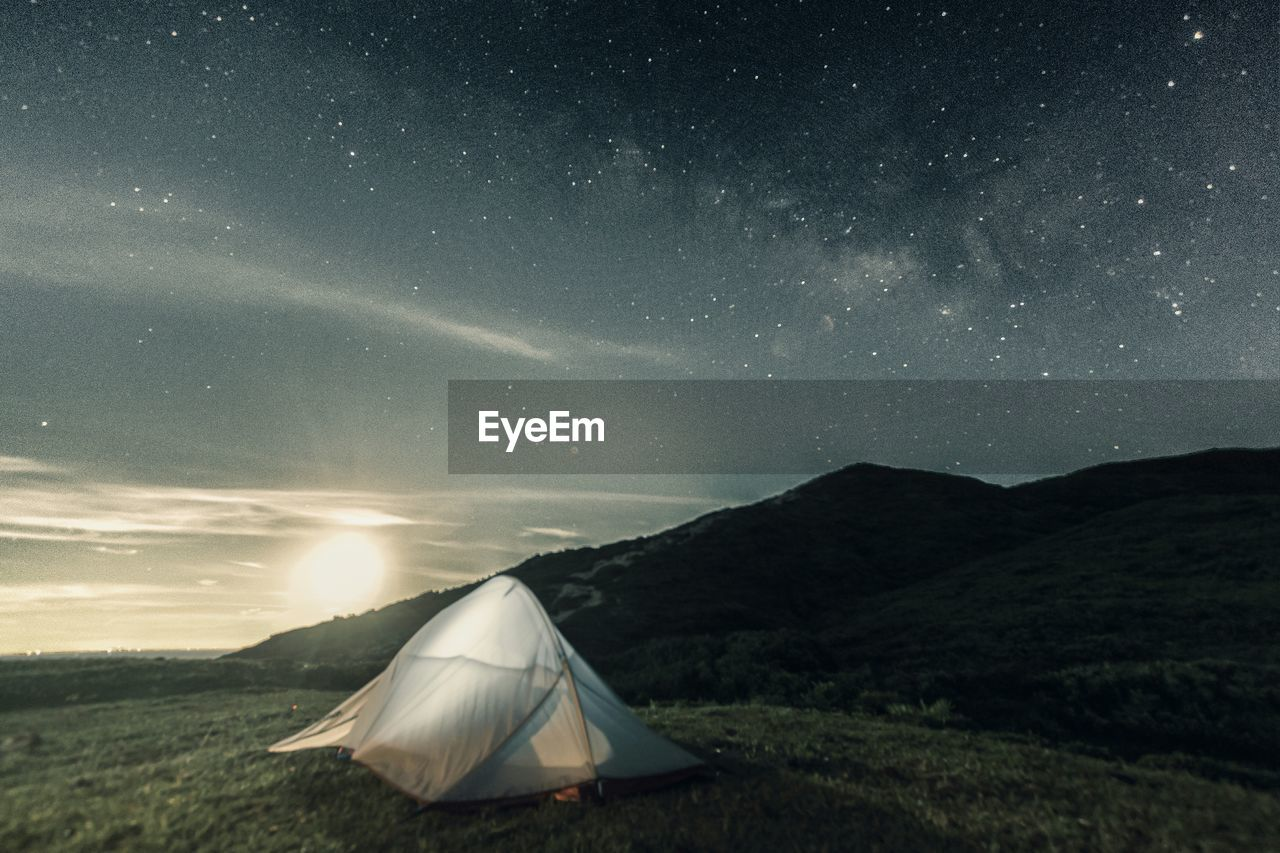 Tent On Grassy Field At Mountain Against Starry Sky