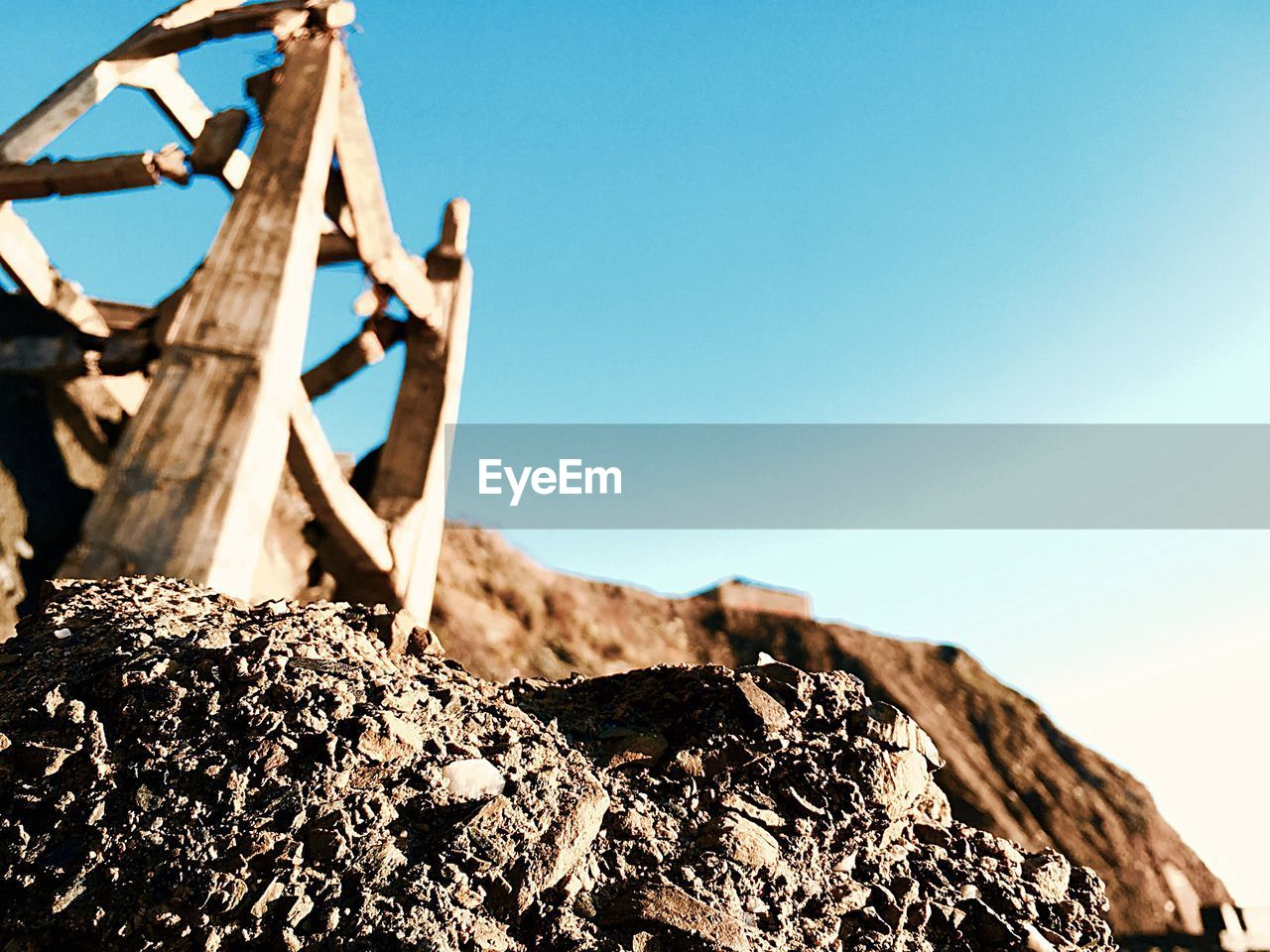 wood - material, clear sky, day, no people, outdoors, sunlight, low angle view, nature, tree stump, close-up, blue, sky