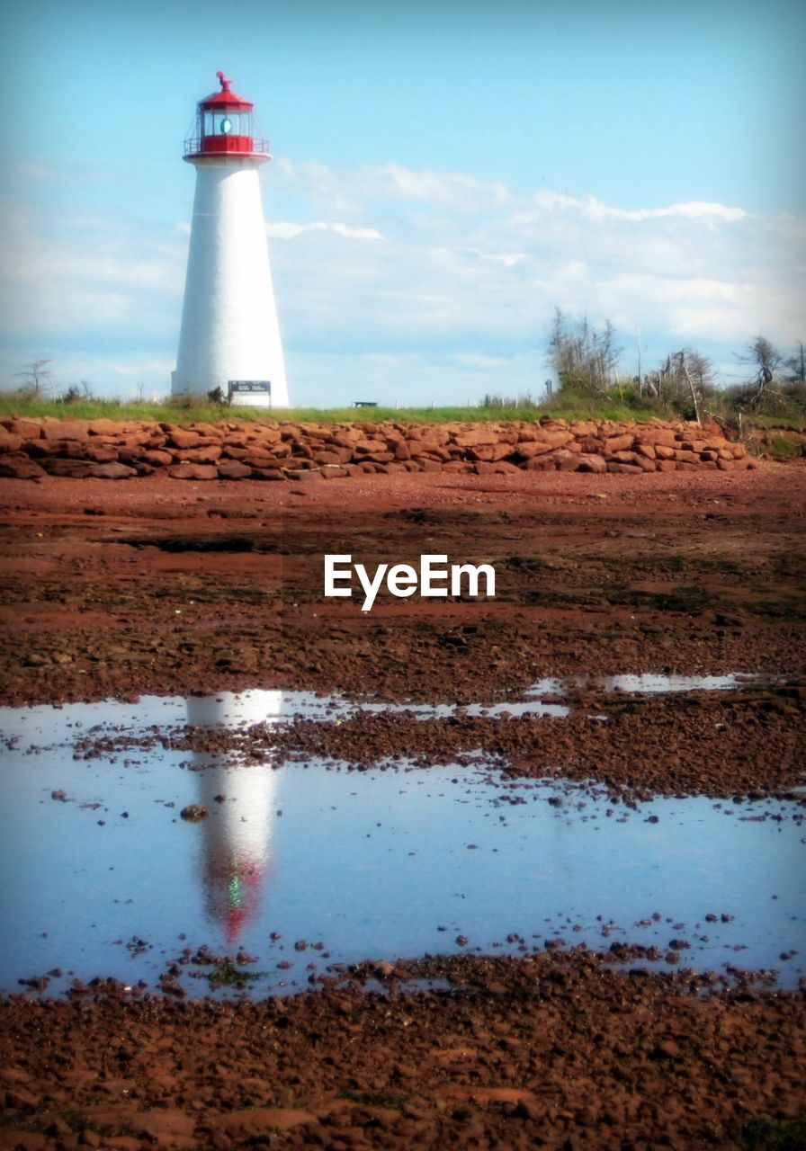 Point Prim Light Station Reflecting In Puddle On Field