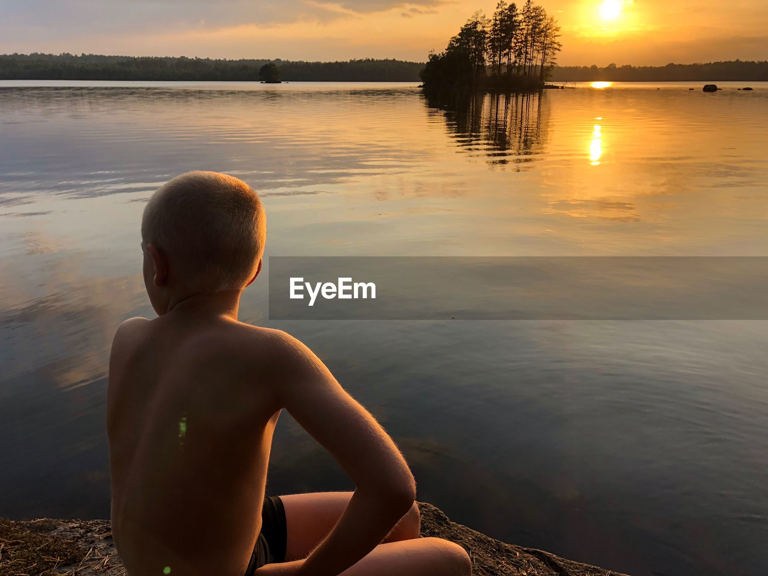 Rear view of shirtless boy looking at lake during sunset