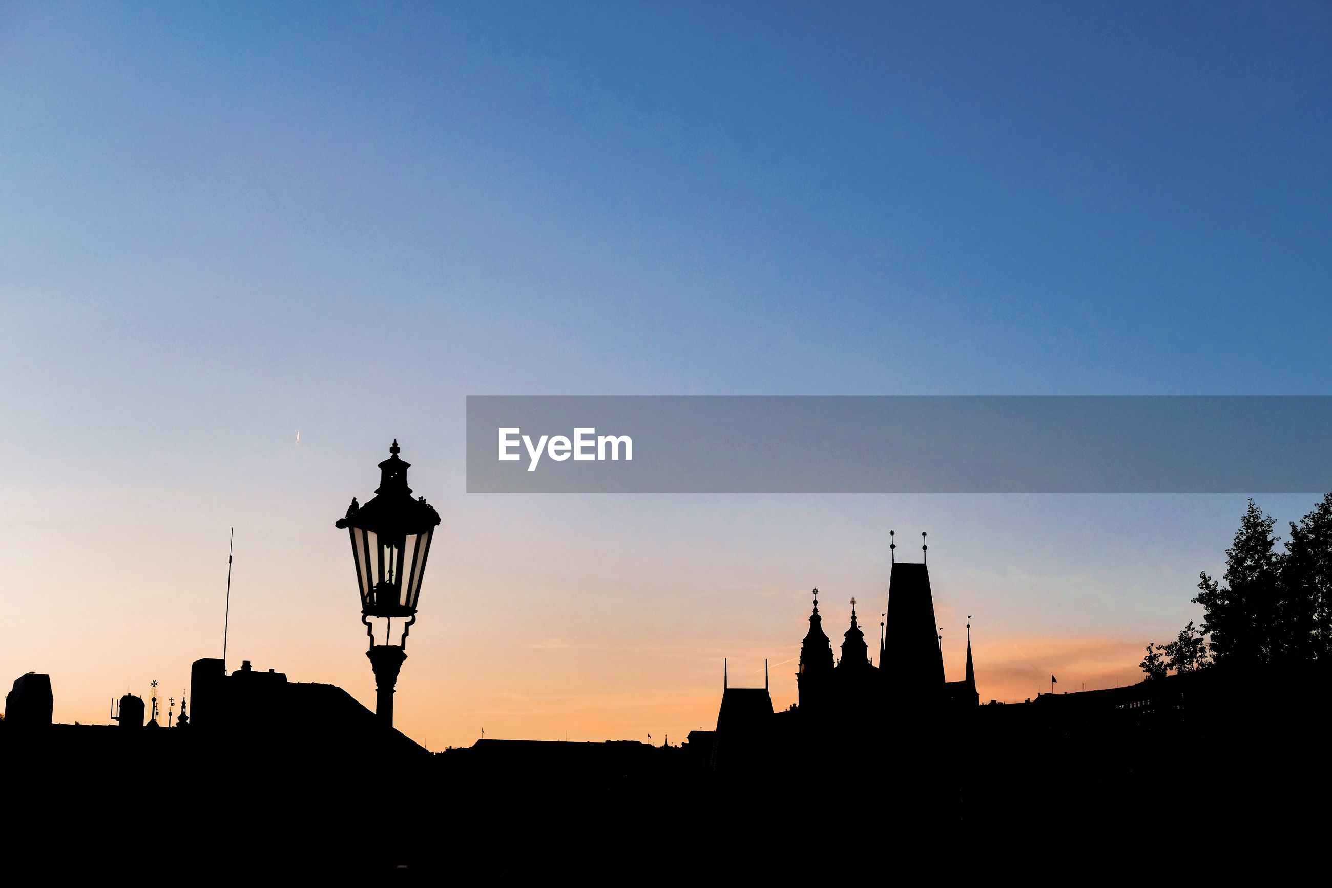 Low angle view of silhouette buildings against sky during sunset - charles bridge in prague