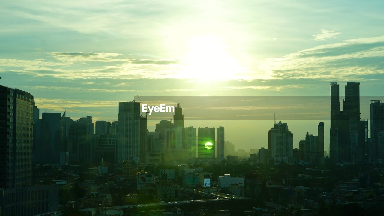 cityscape, architecture, skyscraper, city, building exterior, built structure, modern, sky, sunset, development, skyline, travel destinations, downtown district, city life, urban skyline, cloud - sky, sun, sunlight, no people, growth, tall, outdoors, day