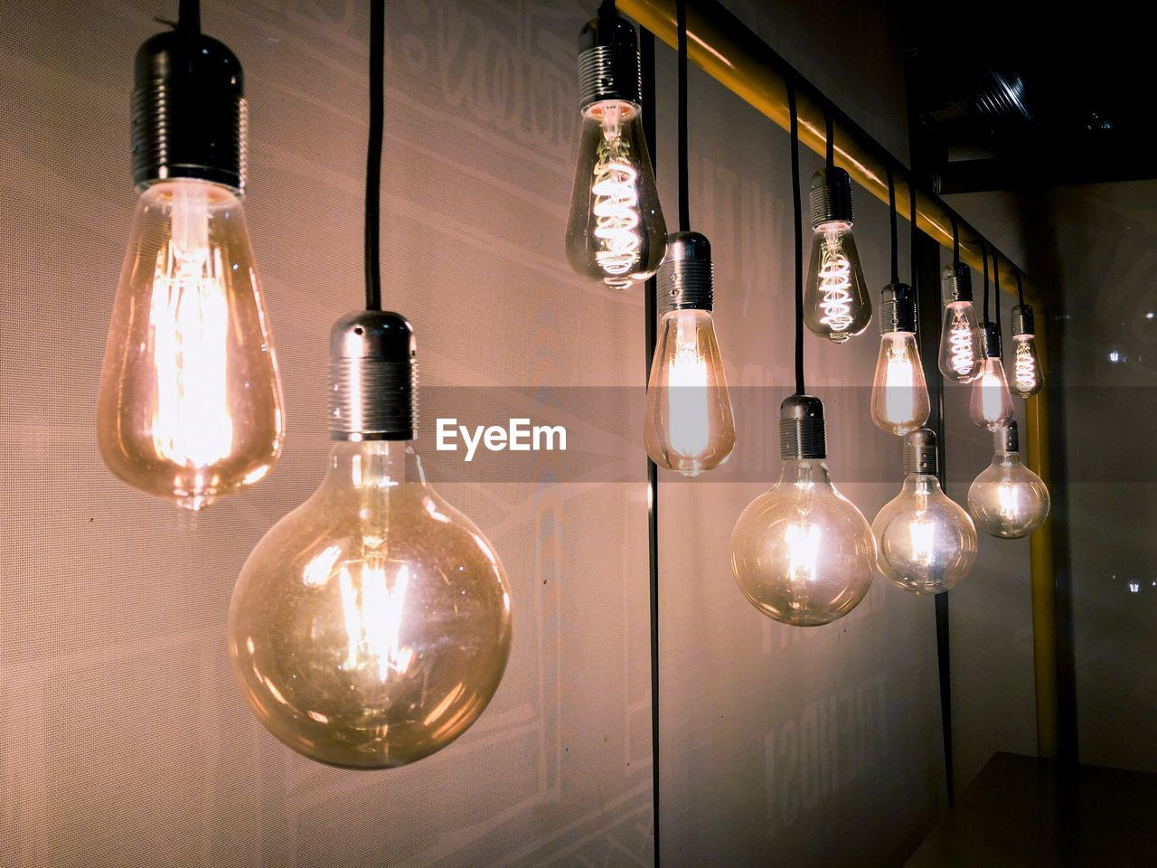 Illuminated light bulbs hanging on wall